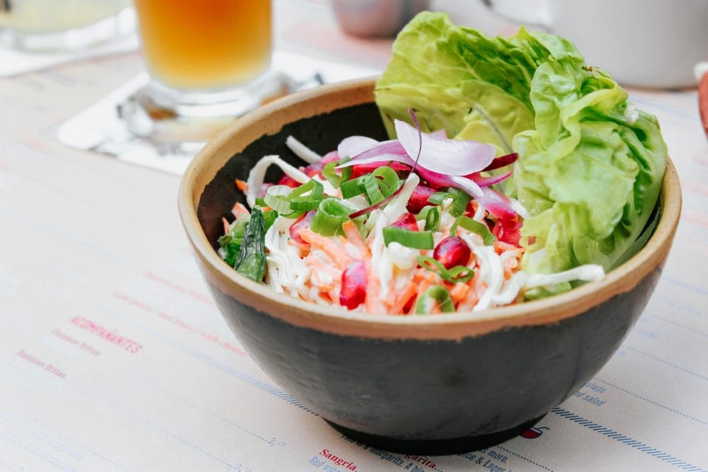 brown bowl containing lettuce and other colourful salad items