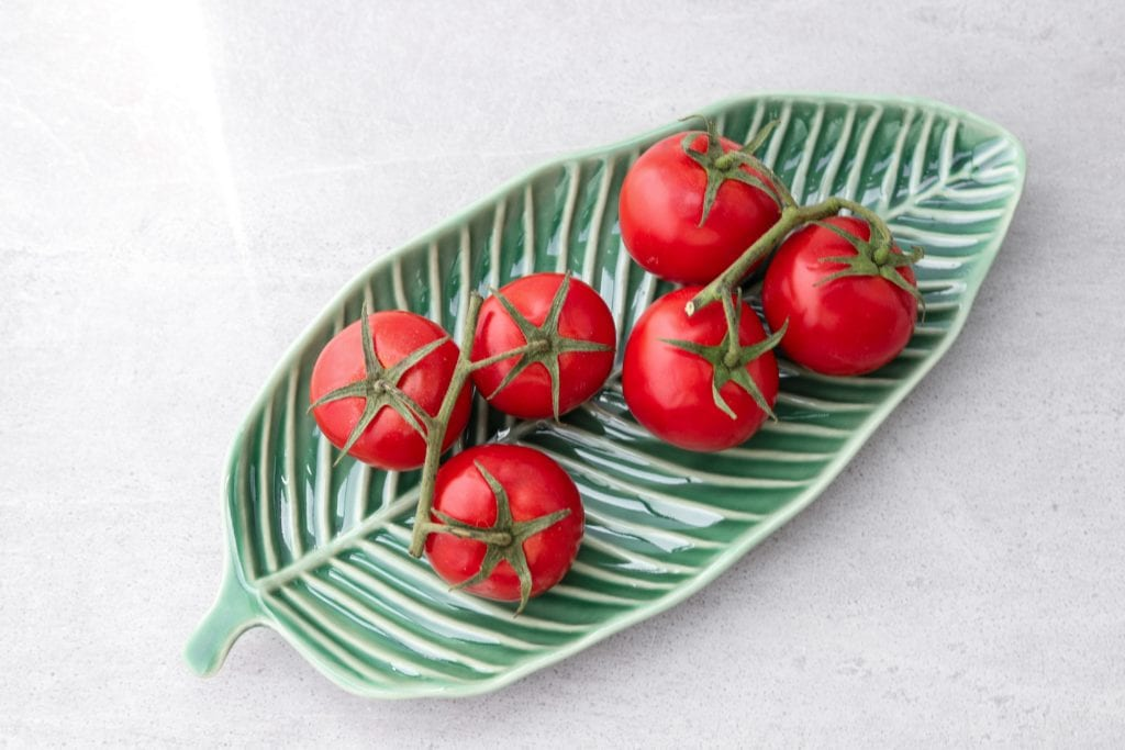 6 cherry tomatoes on a leaf-shaped dish on white background