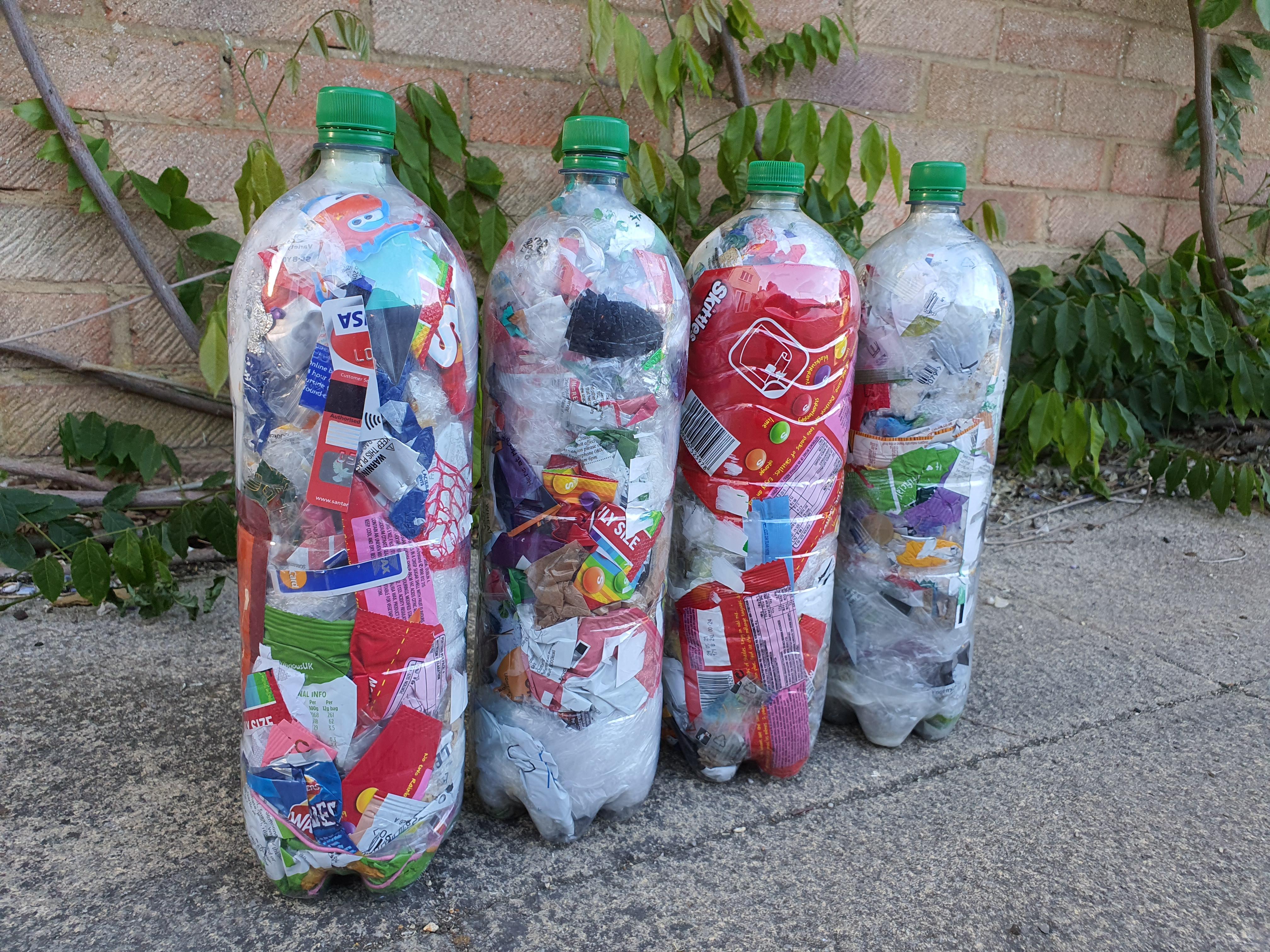 4 plastic bottles made into ecobricks against brick wall background
