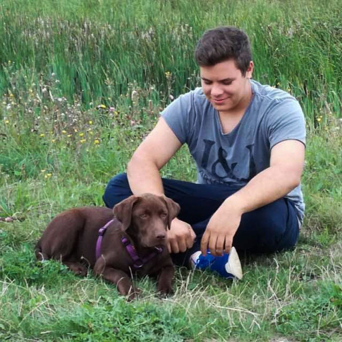 photo of Ailuna app developer Alex with his dog sitting on grass