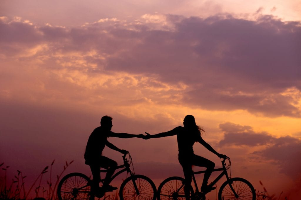 couple on bikes at sunset touching hands