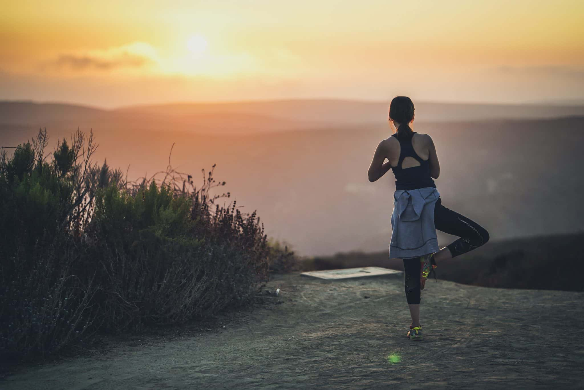 woman doing yoga on a hill at sunrise