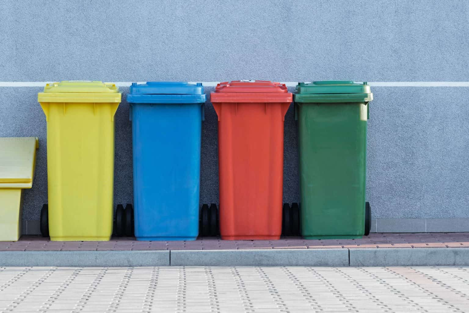 yello, blue, red and green waste bins lined up outside against a wall