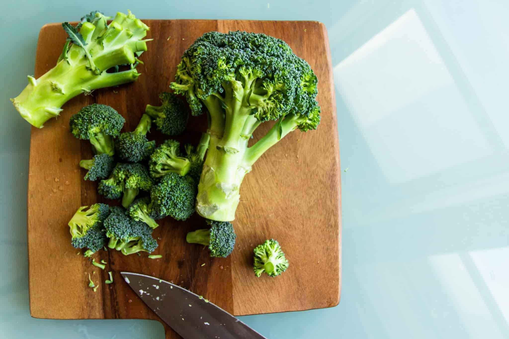 broccoli and a knife on a wooden chopping board