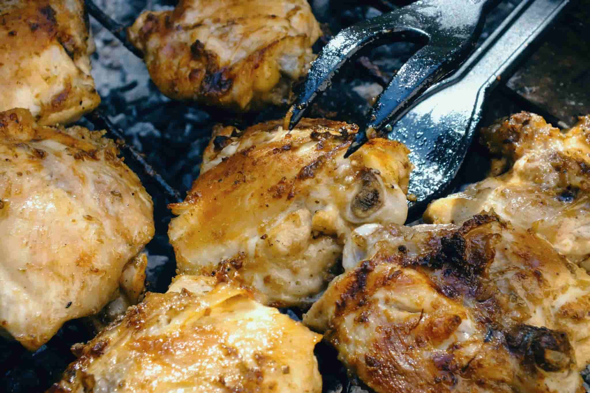 chicken being grilled on a BBQ with tongs in shot