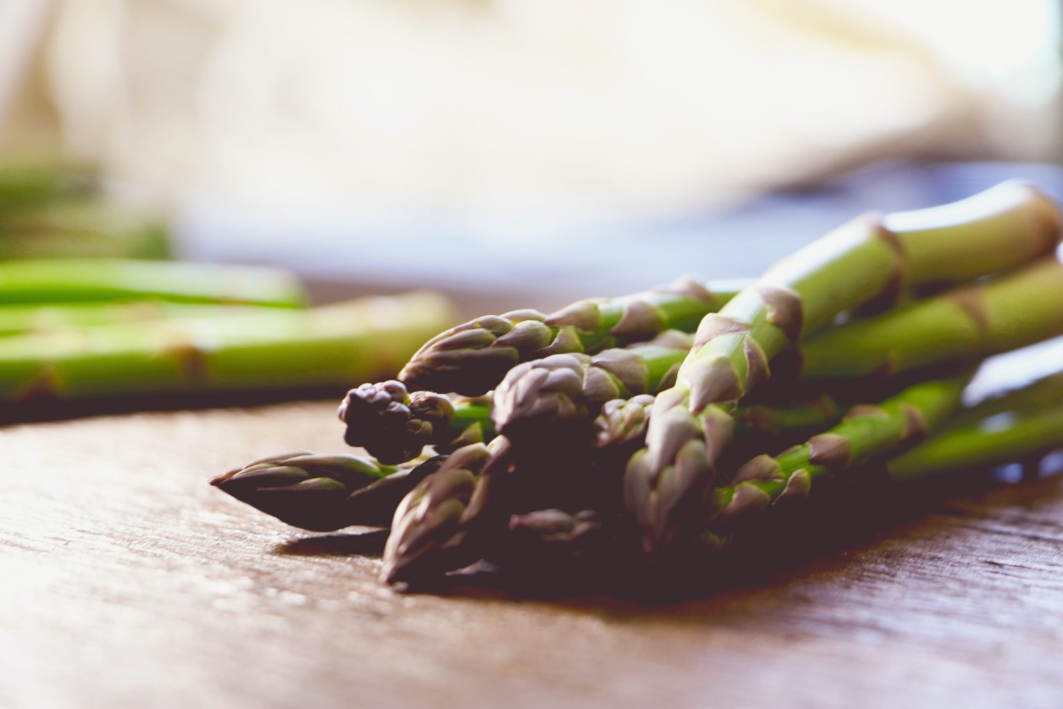 asparagus spears on a wooden chopping board