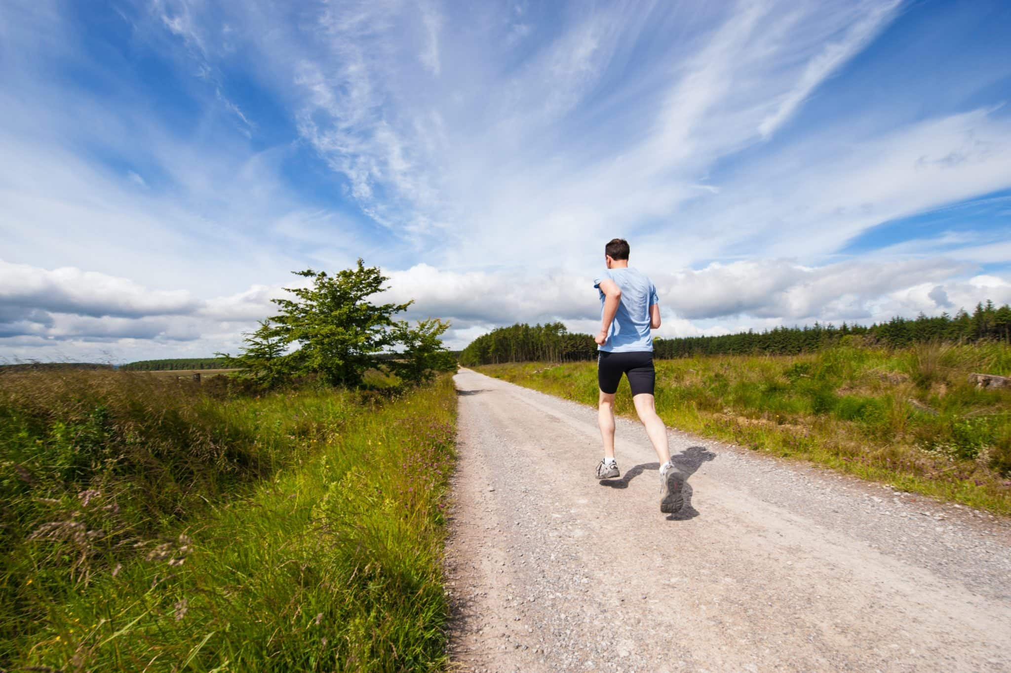 man running along long straight gravel path with grass either side