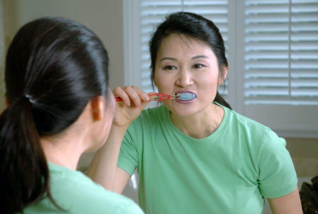 lady in green t shirt brushing teeth in mirror