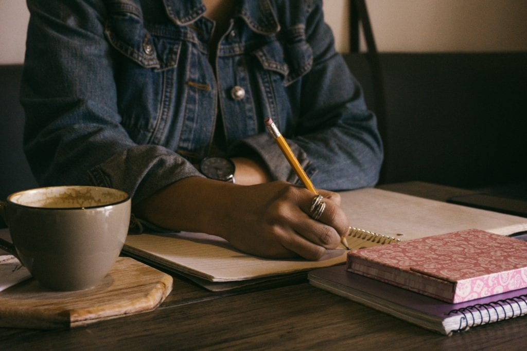 person writing in notepad with coffee and books on table