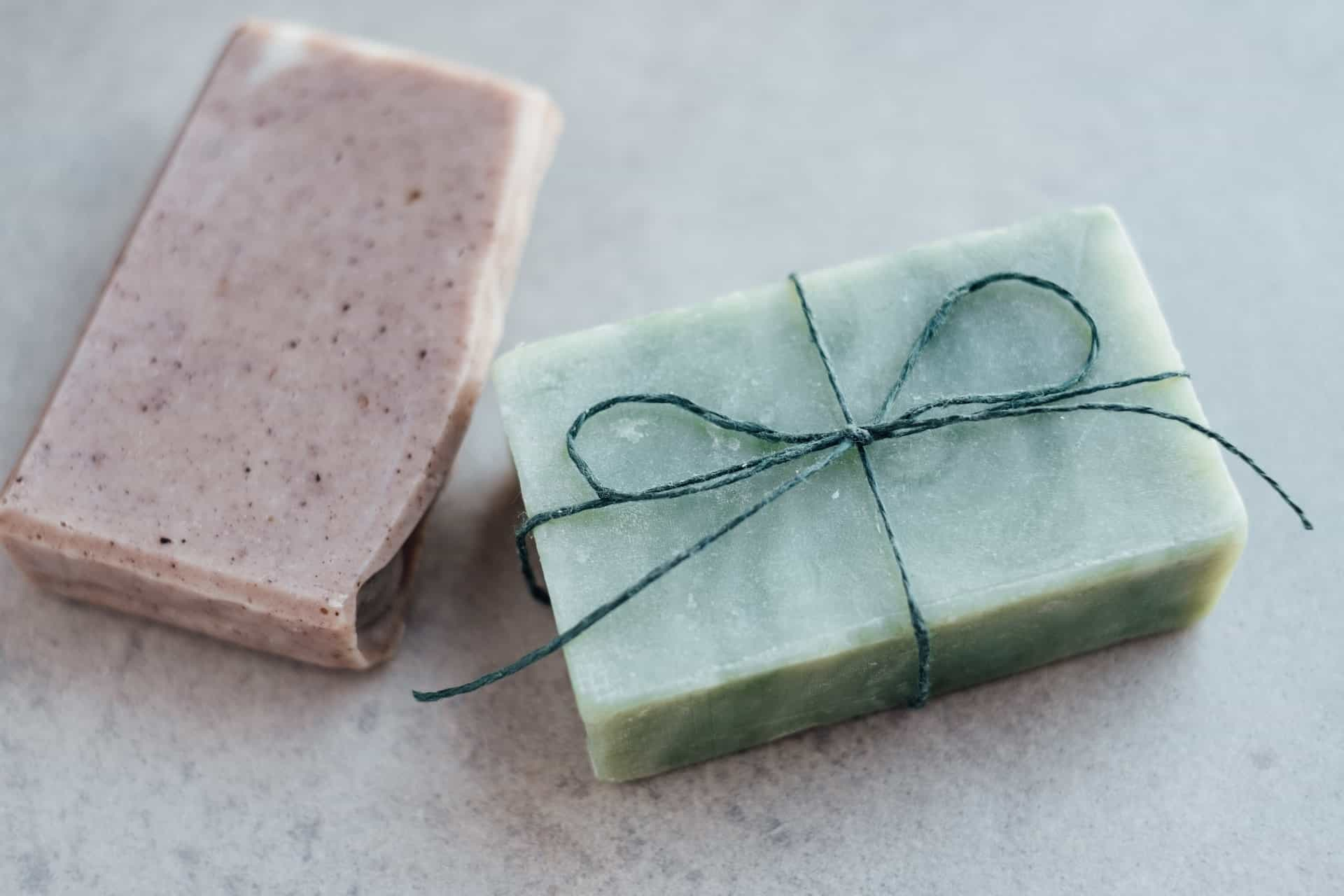 solid shampoo bars in pink and brown on a light blue surface