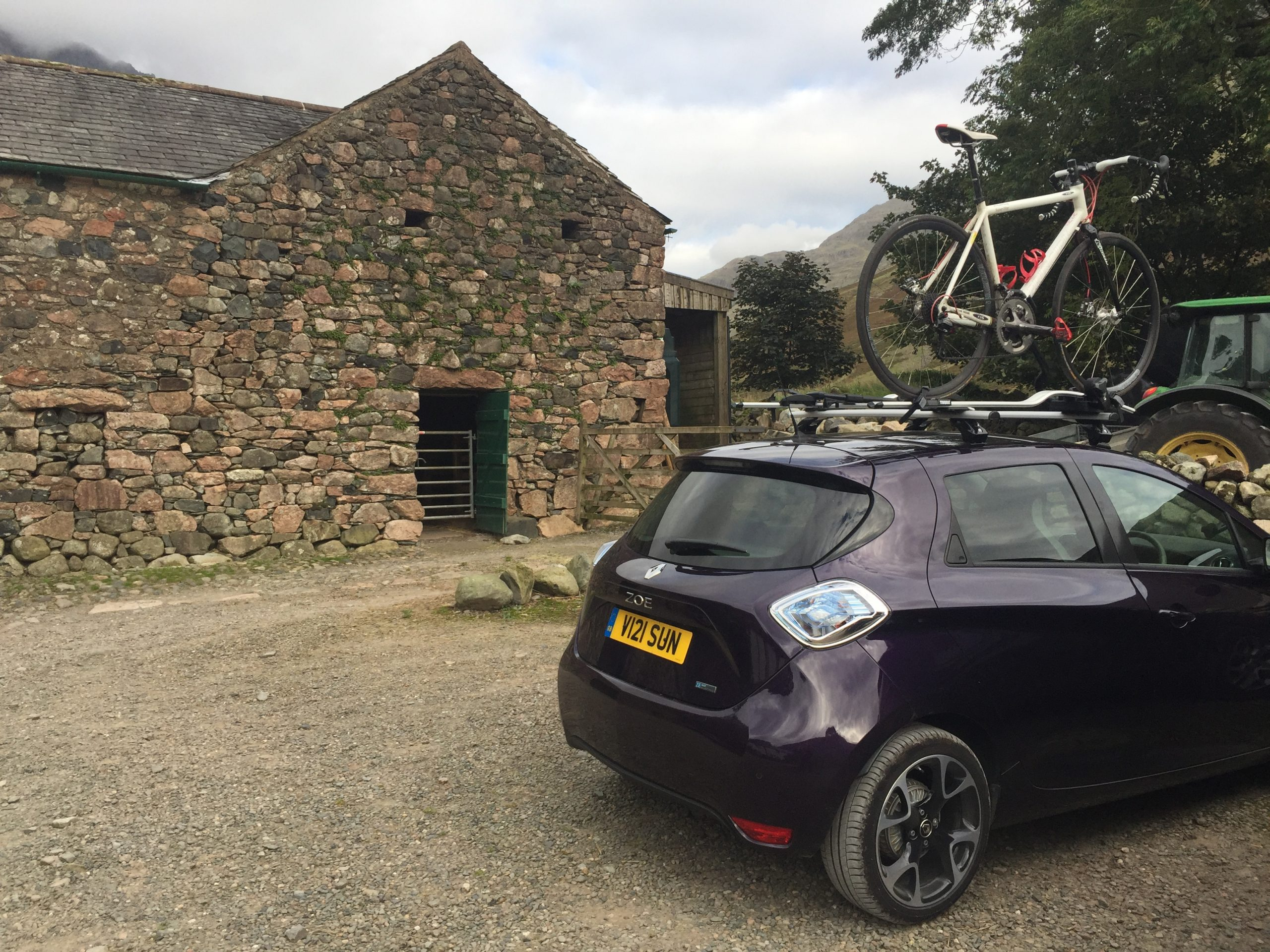 Renault zoe parked in front of a Yorkshire farm style building with a bike on its roof
