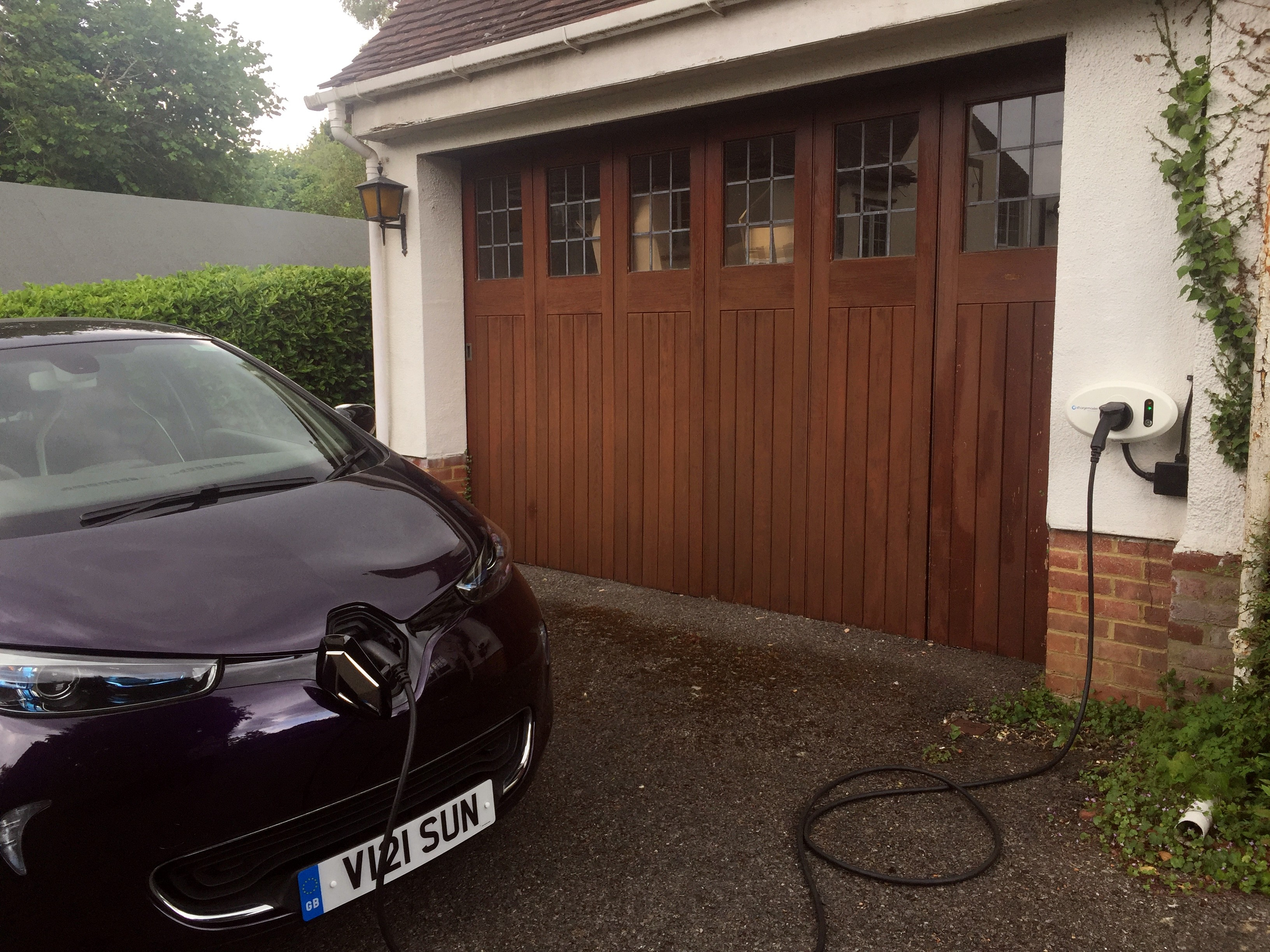 renault Zoe charging at home in front of brown garage door
