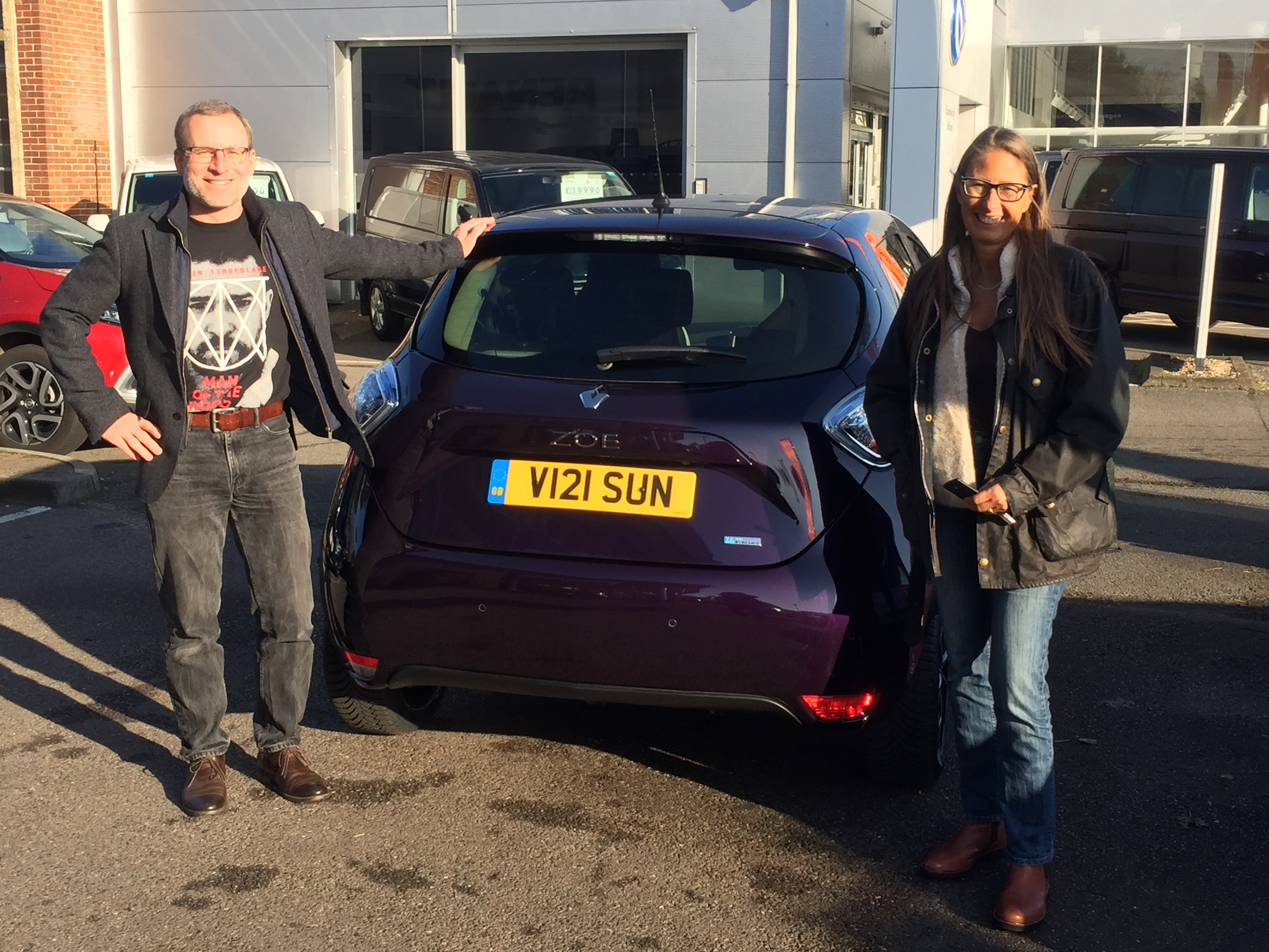 Lars and Helene standing to the rear of their purple electric car, smiling happily with their purchase