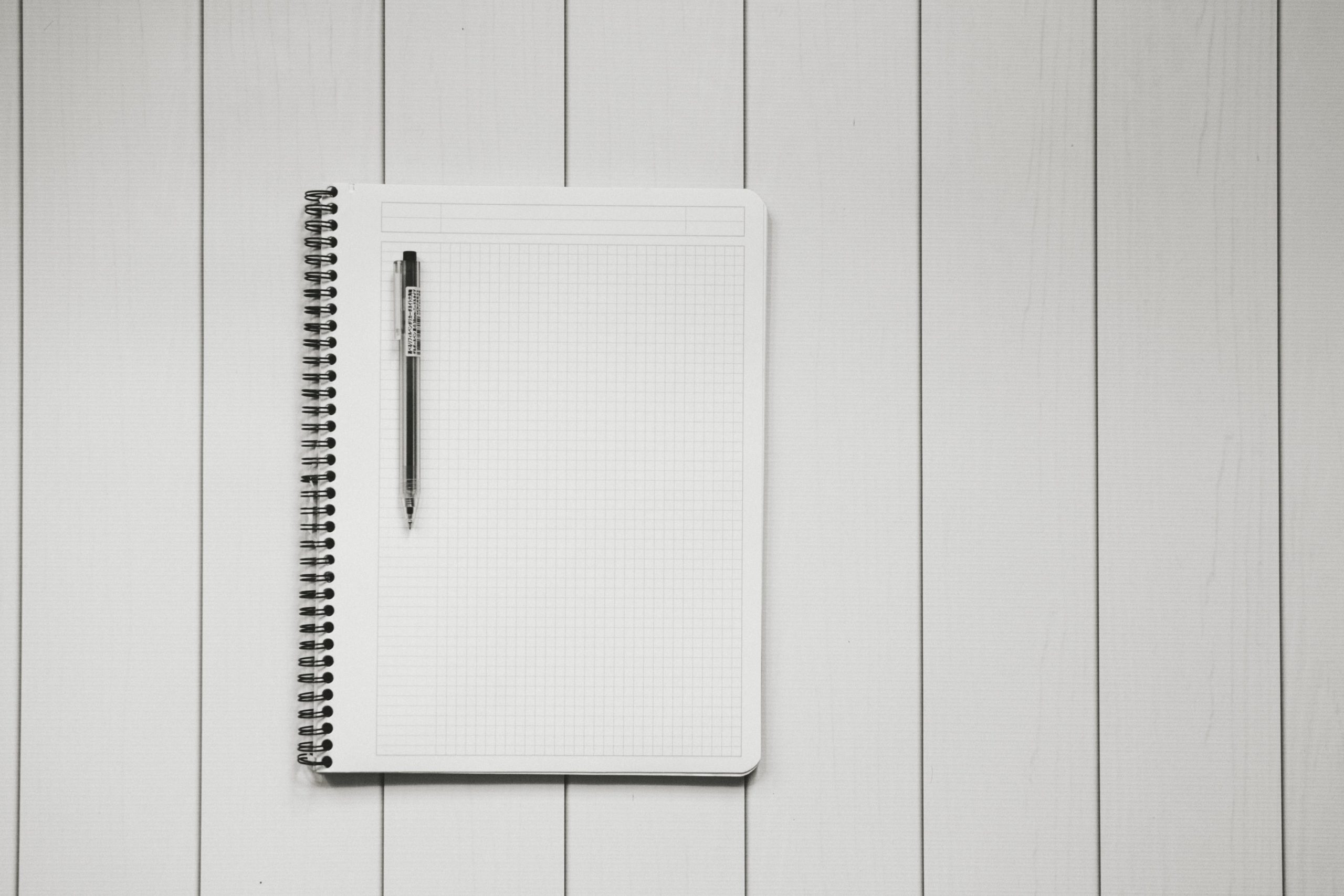 waste check - blank notepad and pen on a white wooden surface
