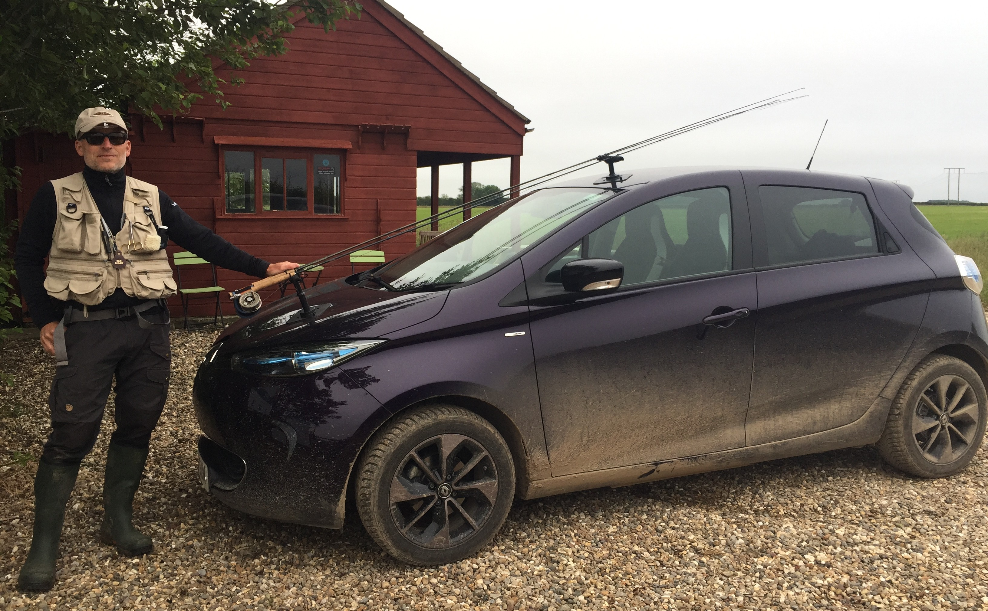 living with an EV - Lars standing next to his EV in fishing gear with a fishing rod attached to the car