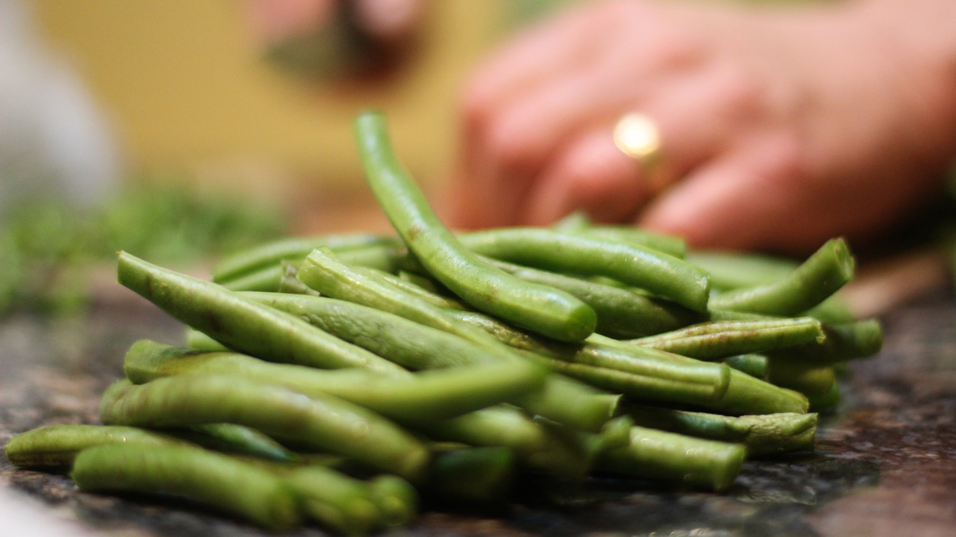person chopping French beans, whicb are in season in the UK in June