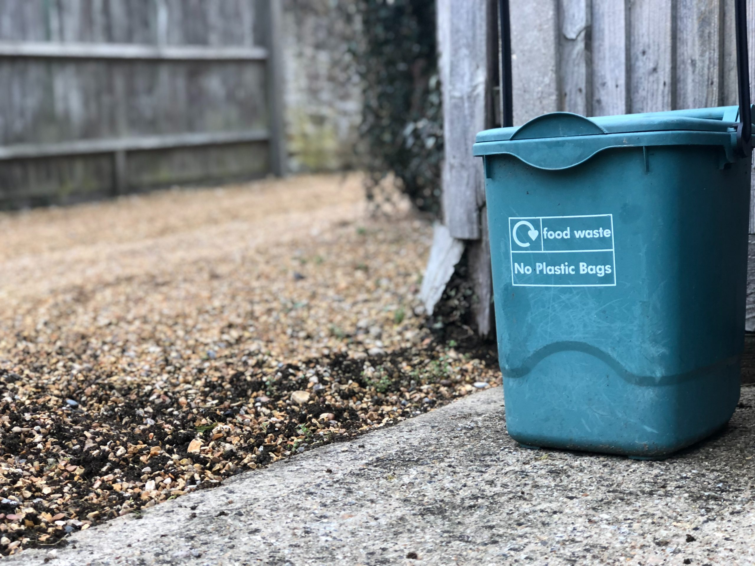 Green food waste bin standing outside against a fence