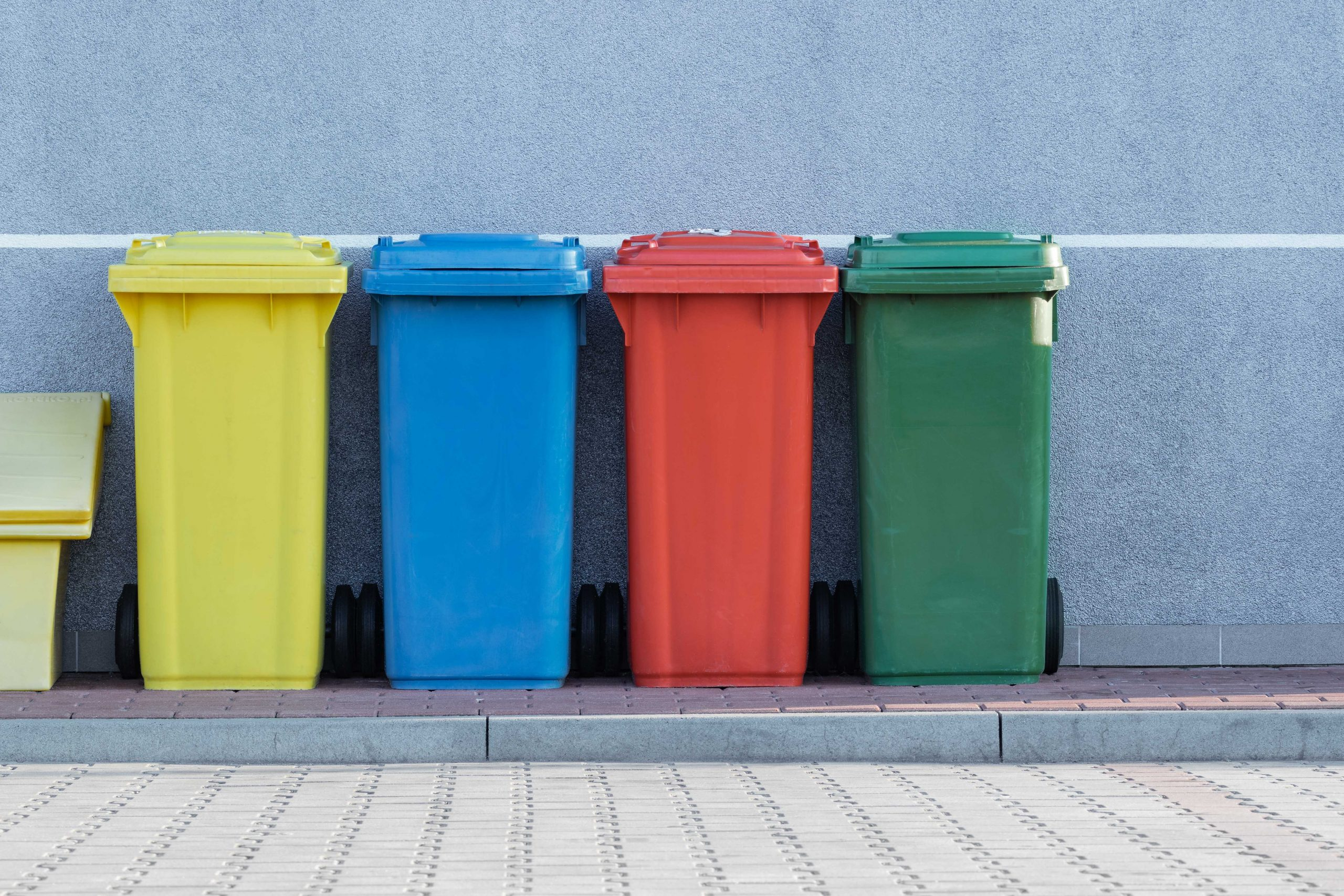 yellow, blue, red and green waste bins lined up against a wall