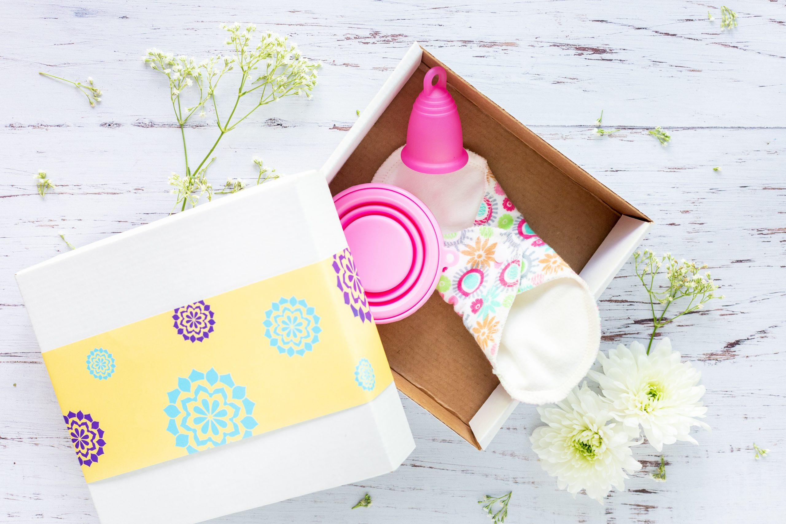 A white and yellow box sits on a white table, containing a pink mentrual cup, a reusable sanitary pad and a small pink pot
