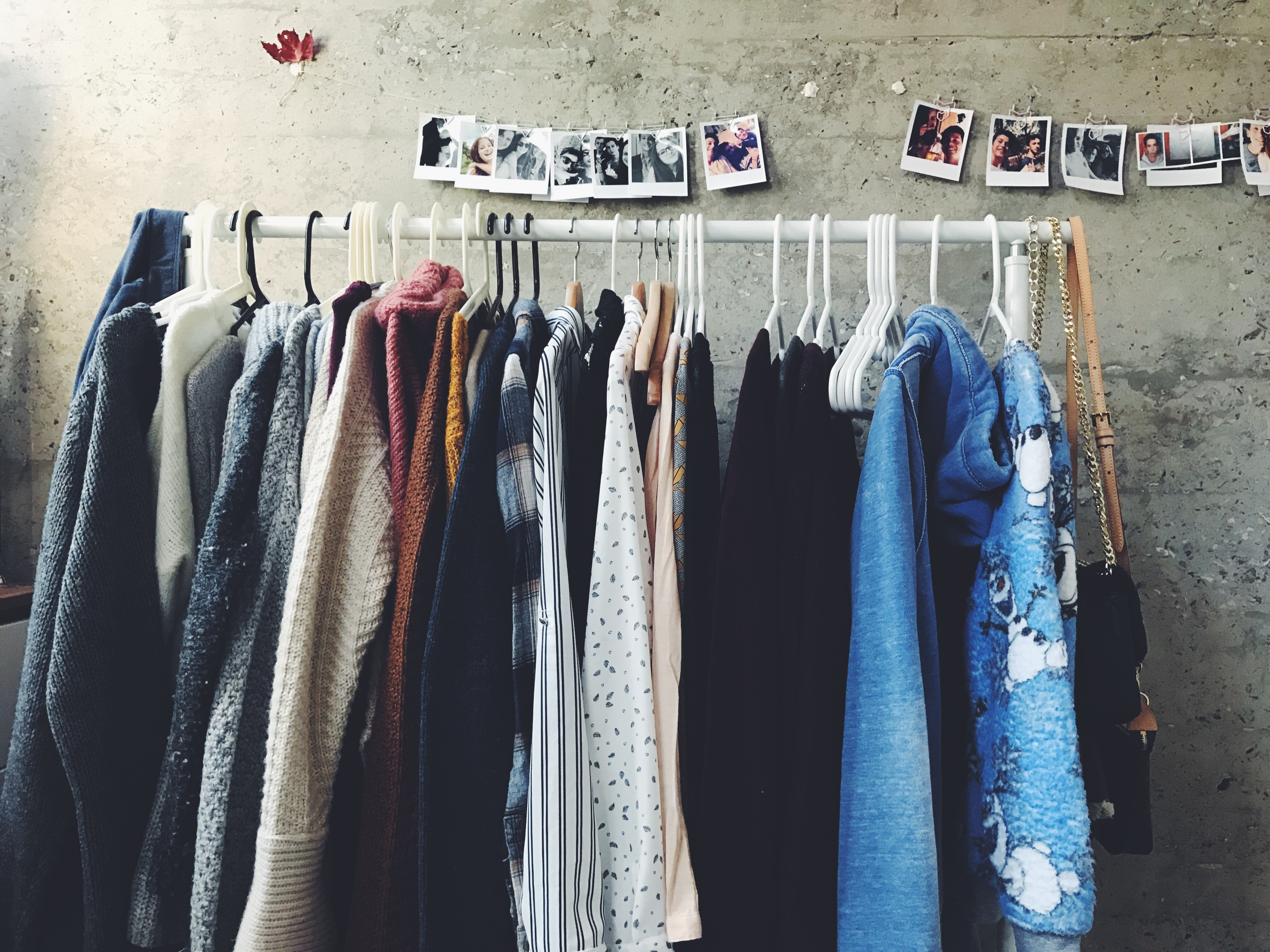 Rail of clothes in neutral colours with polaroid-style photos hanging above