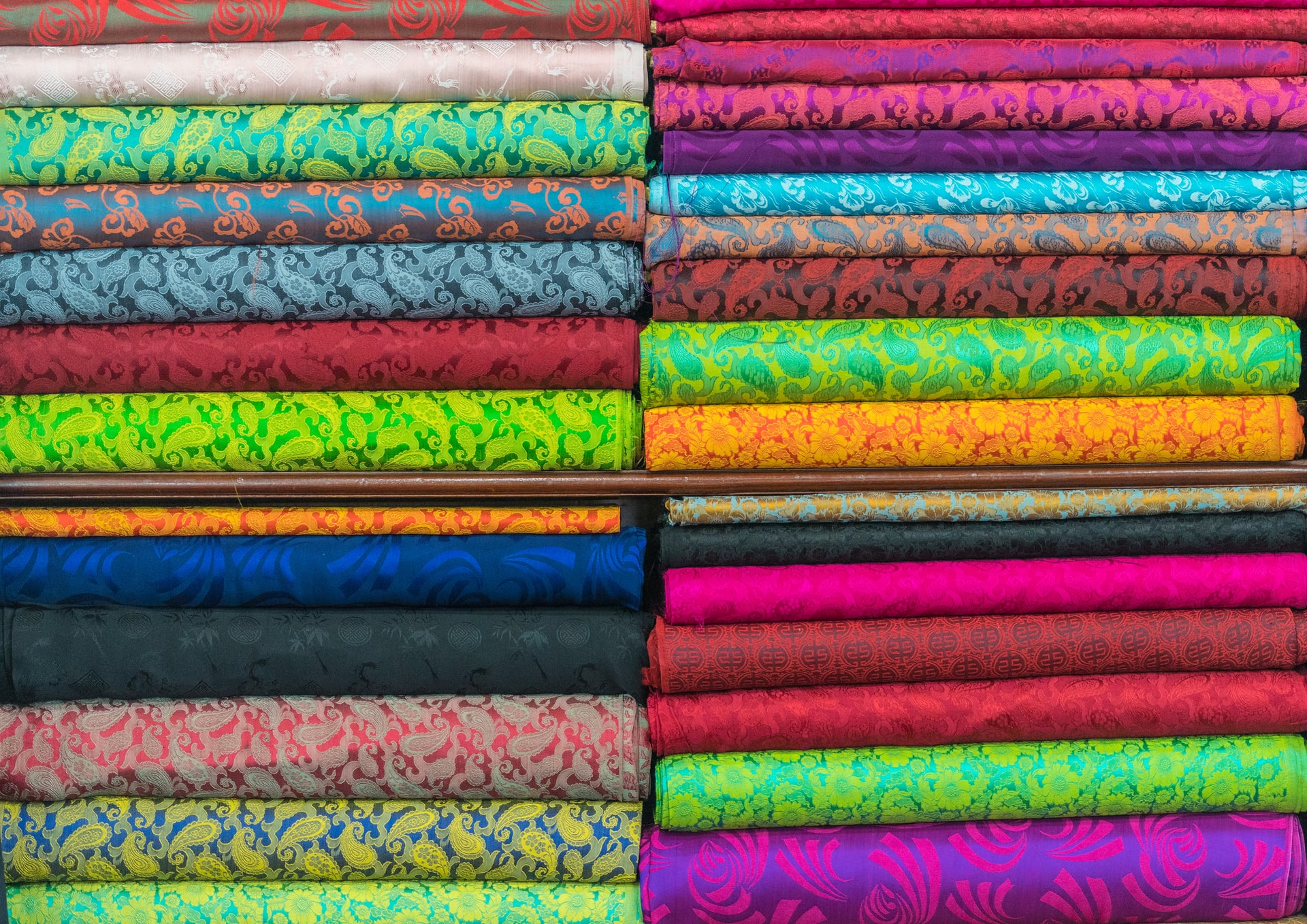 sustainable fashion - two piles of brightly-coloured fabric
