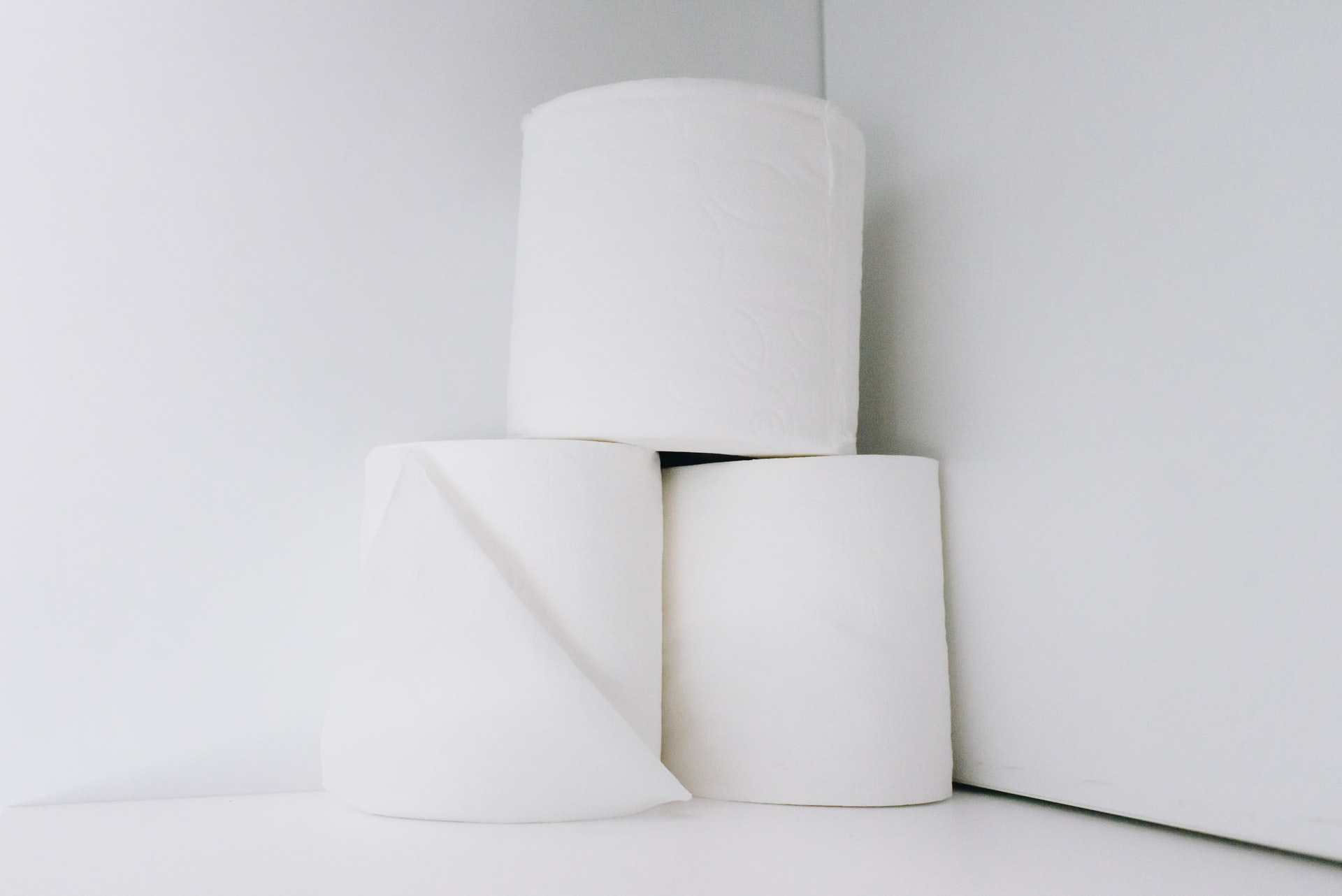 three white toilet rolls stacked against a white background