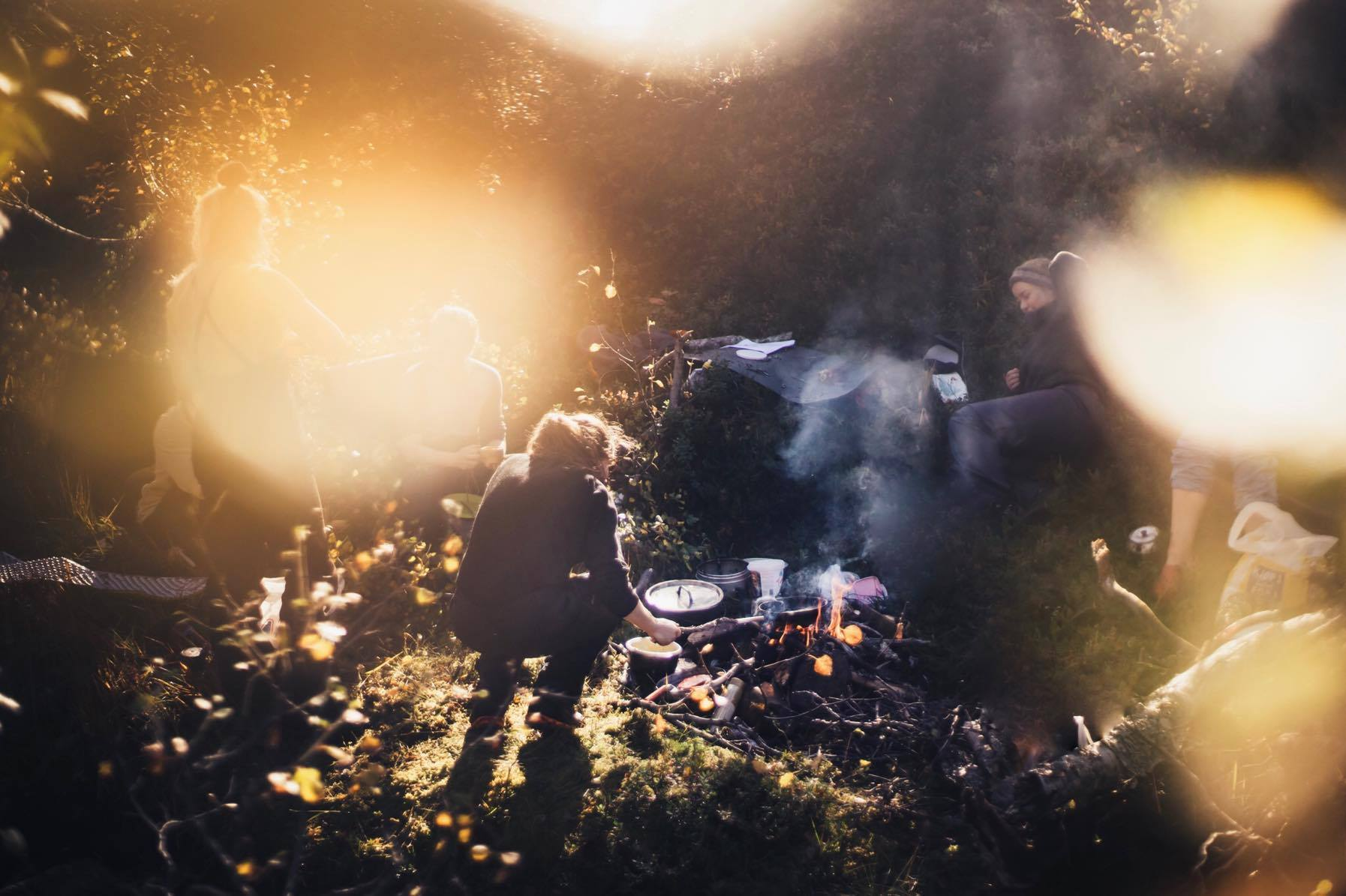 Friluftsliv - a group of friends around a campfire - the photo has some lens flare, suggesting early morning or early evening