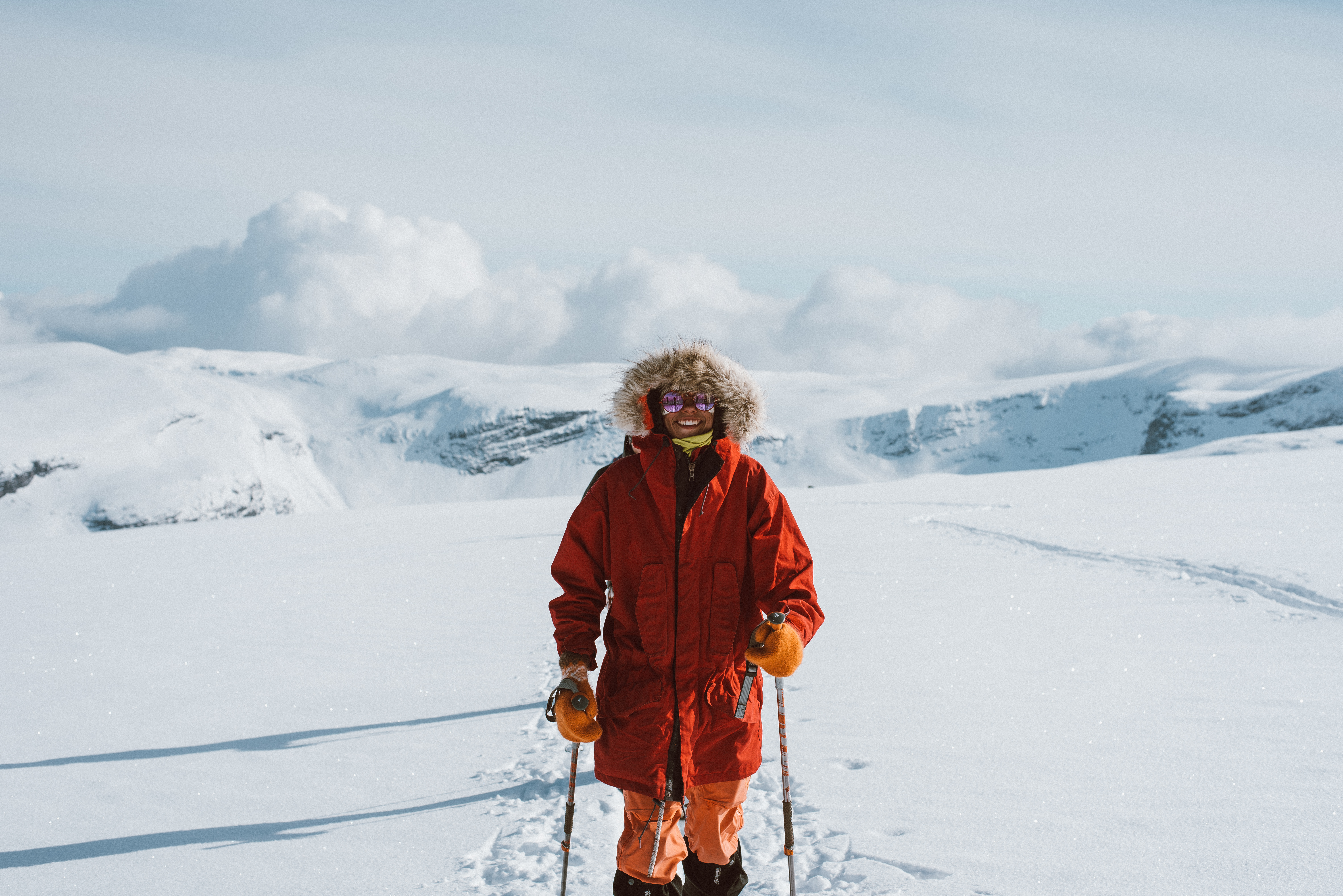 person in a red hooded coat in a snowy scene smiling with walking poles