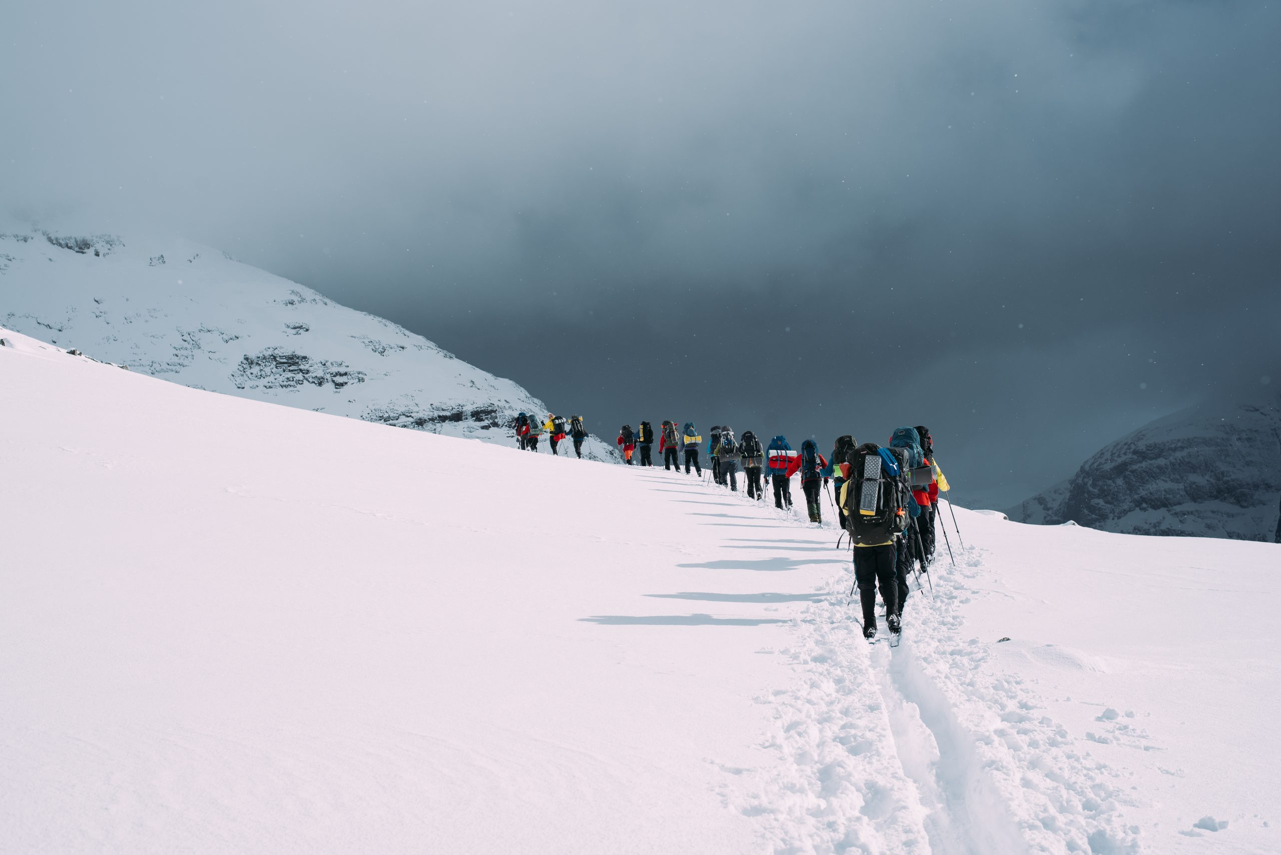 a long line of hikers walking into the distance in the snow