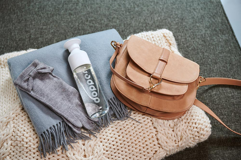 dopper glass bottle next to a brown satchel on a folded scarf