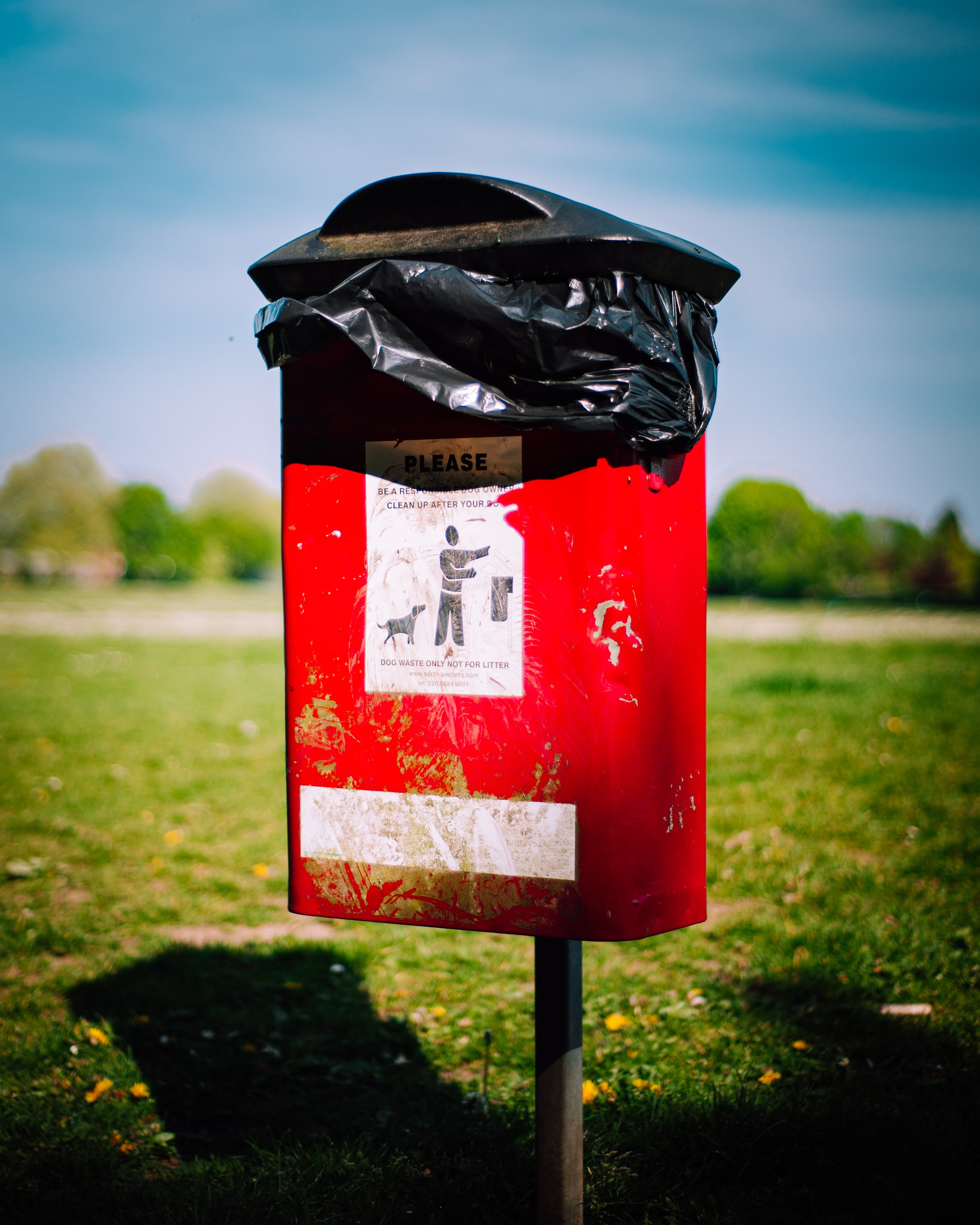 red dog poo bin on a field in daytime