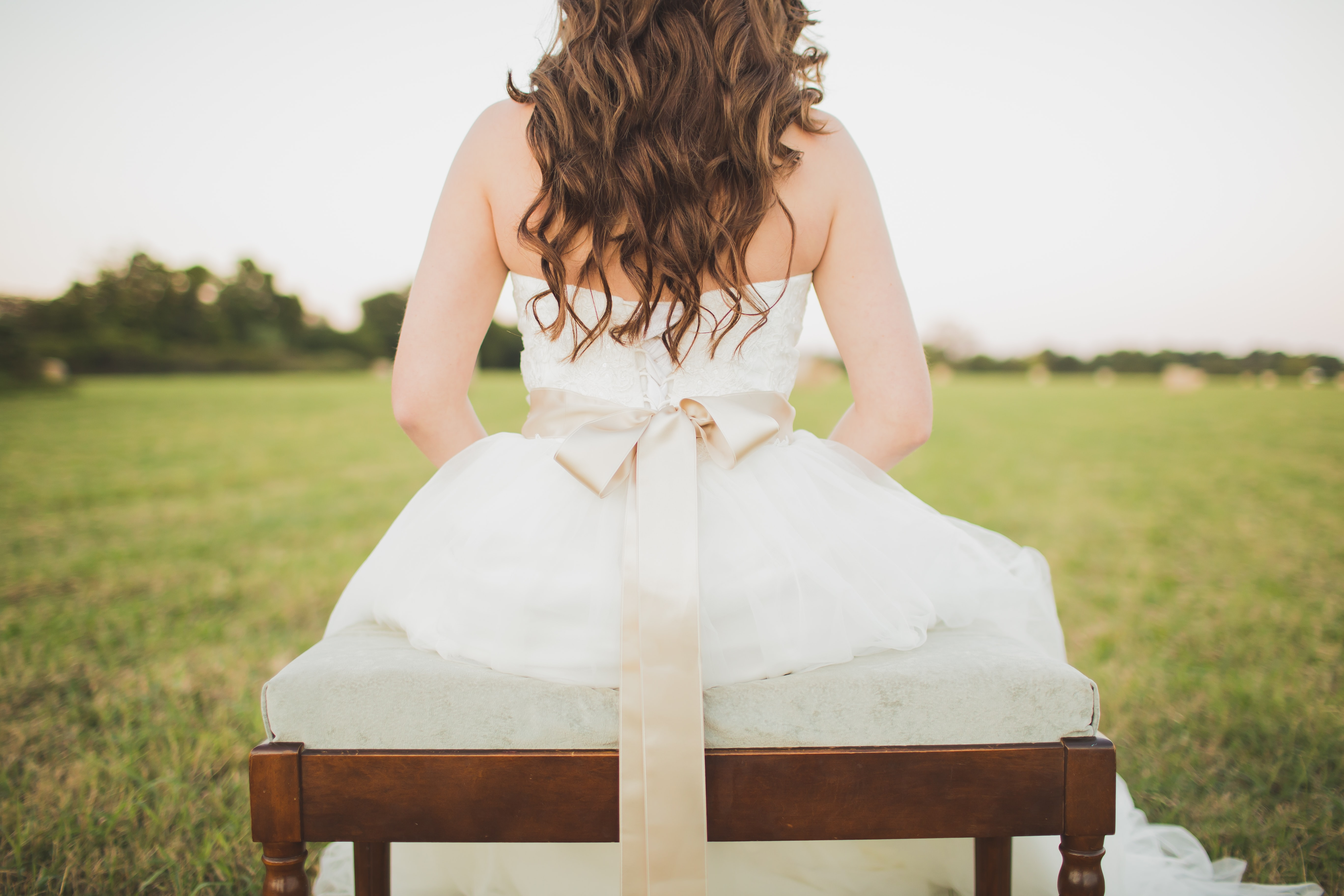bride sitting with her back to camera on a bench