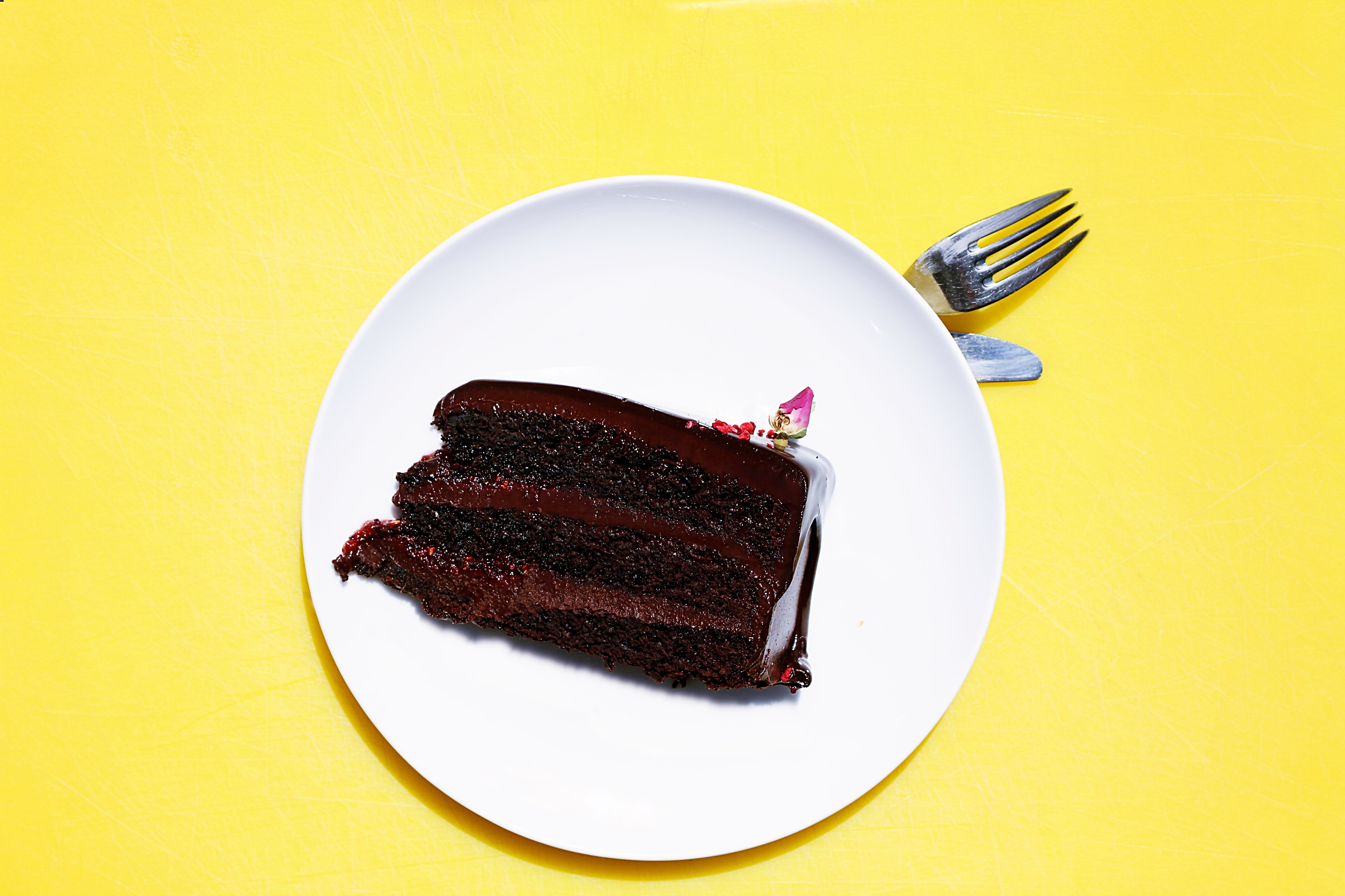 slice of chocolate cake on a white plate on a yellow surface