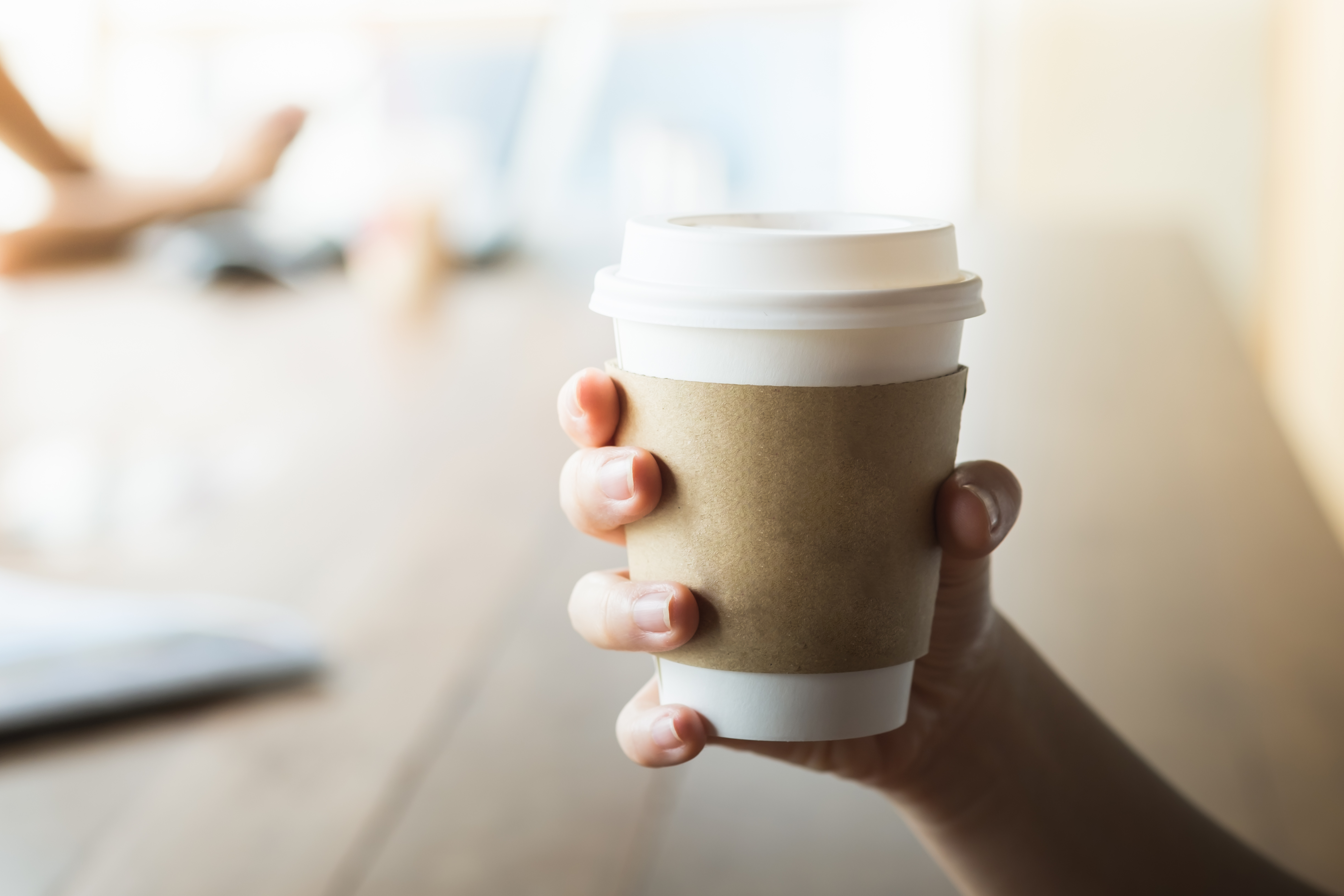 how to recycle coffee cups and sleeves - person holding a coffee cup