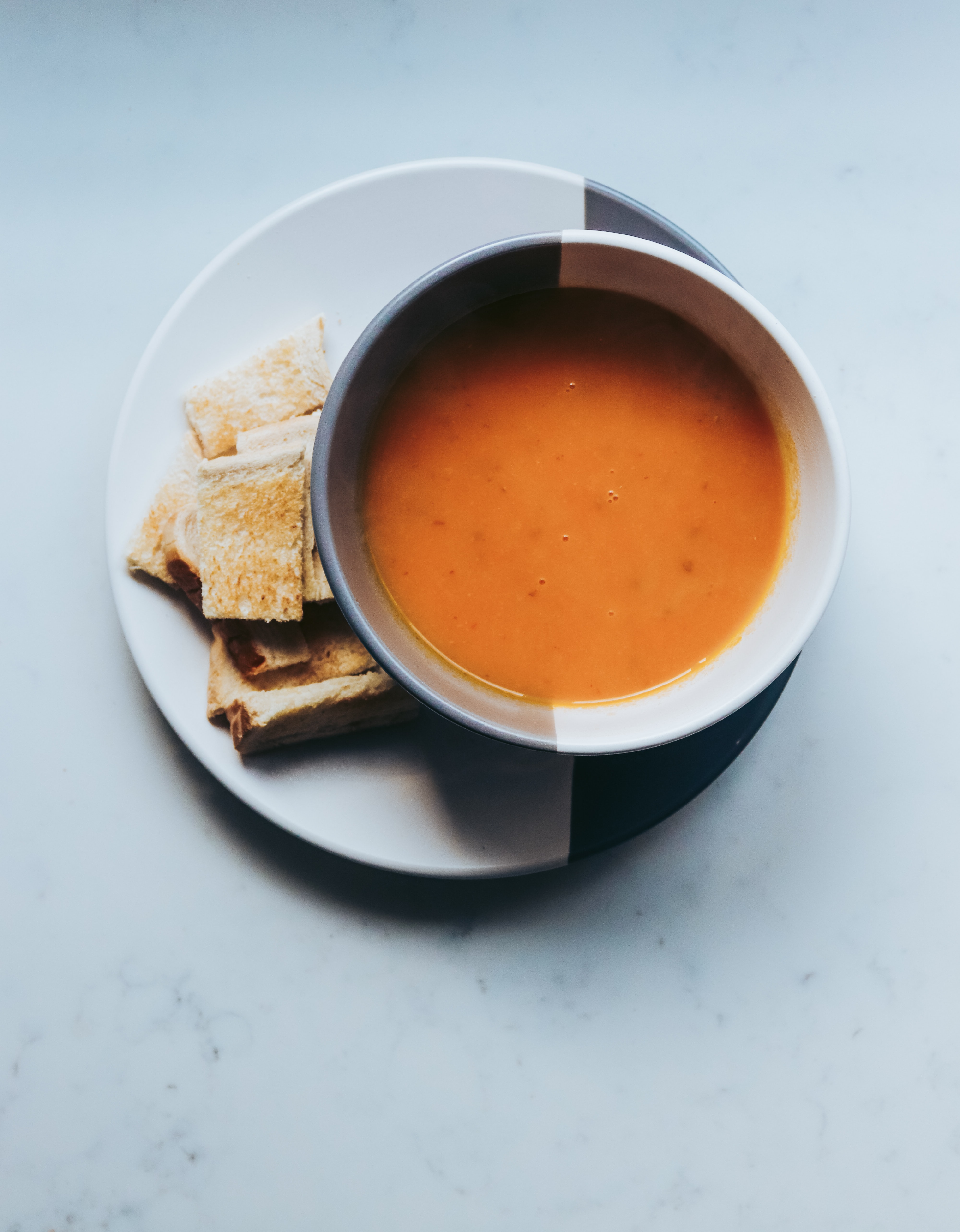 butternut squash soup in a bowl with toast on the side