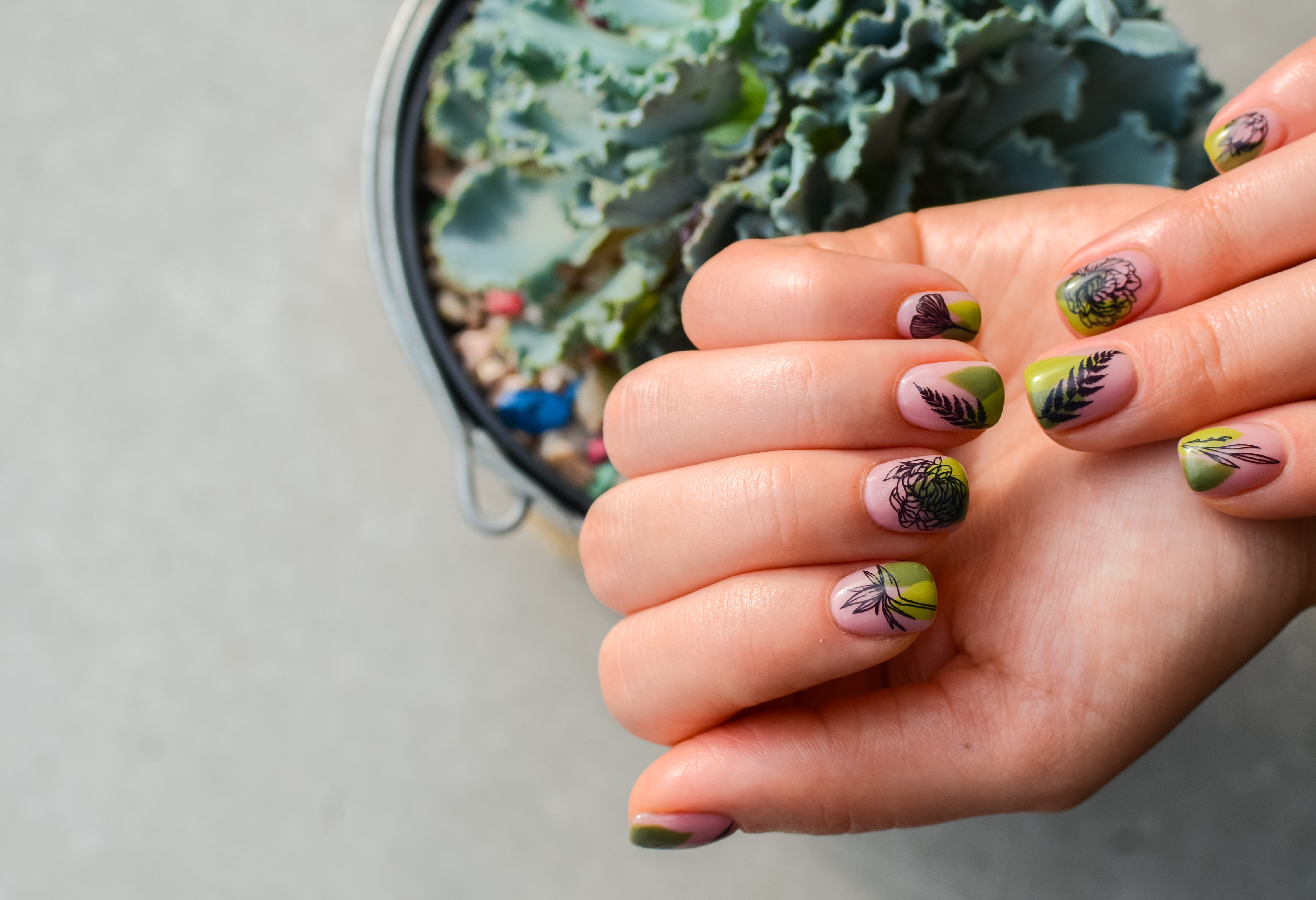 intricately decorated green themed manicure
