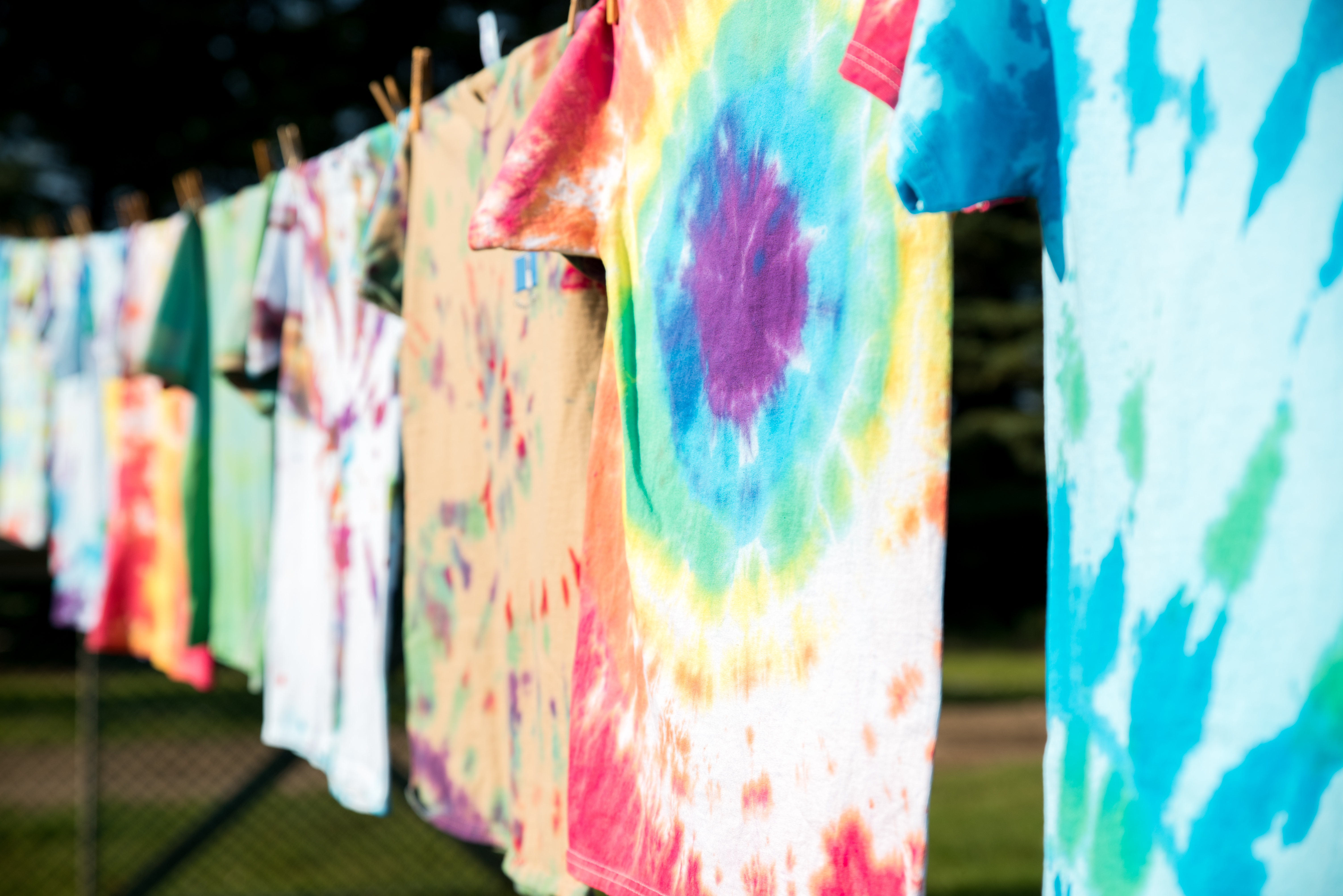 brightly coloured tie-die t shirts hanging out to dry