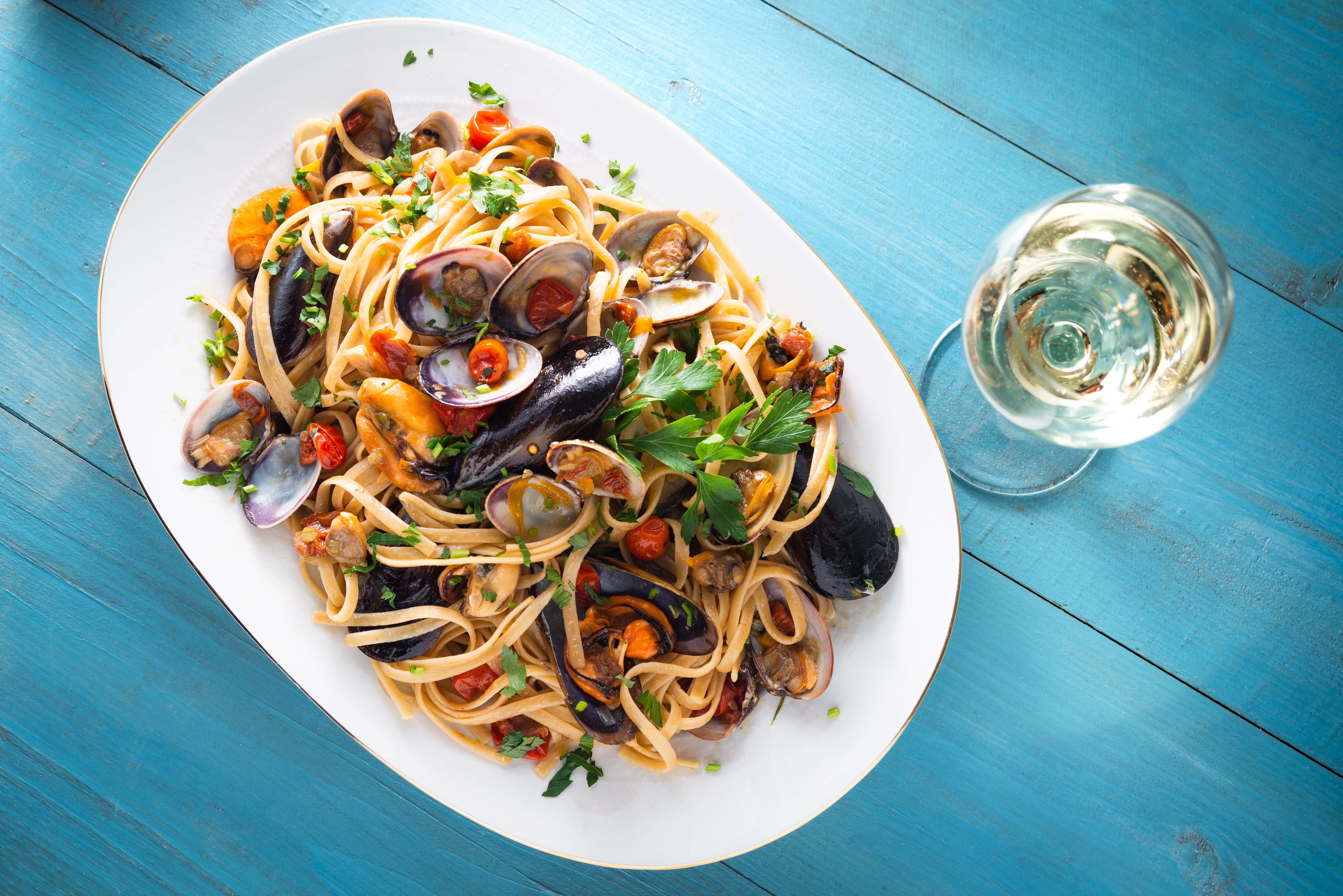 clam linguine on a white plate with blue background