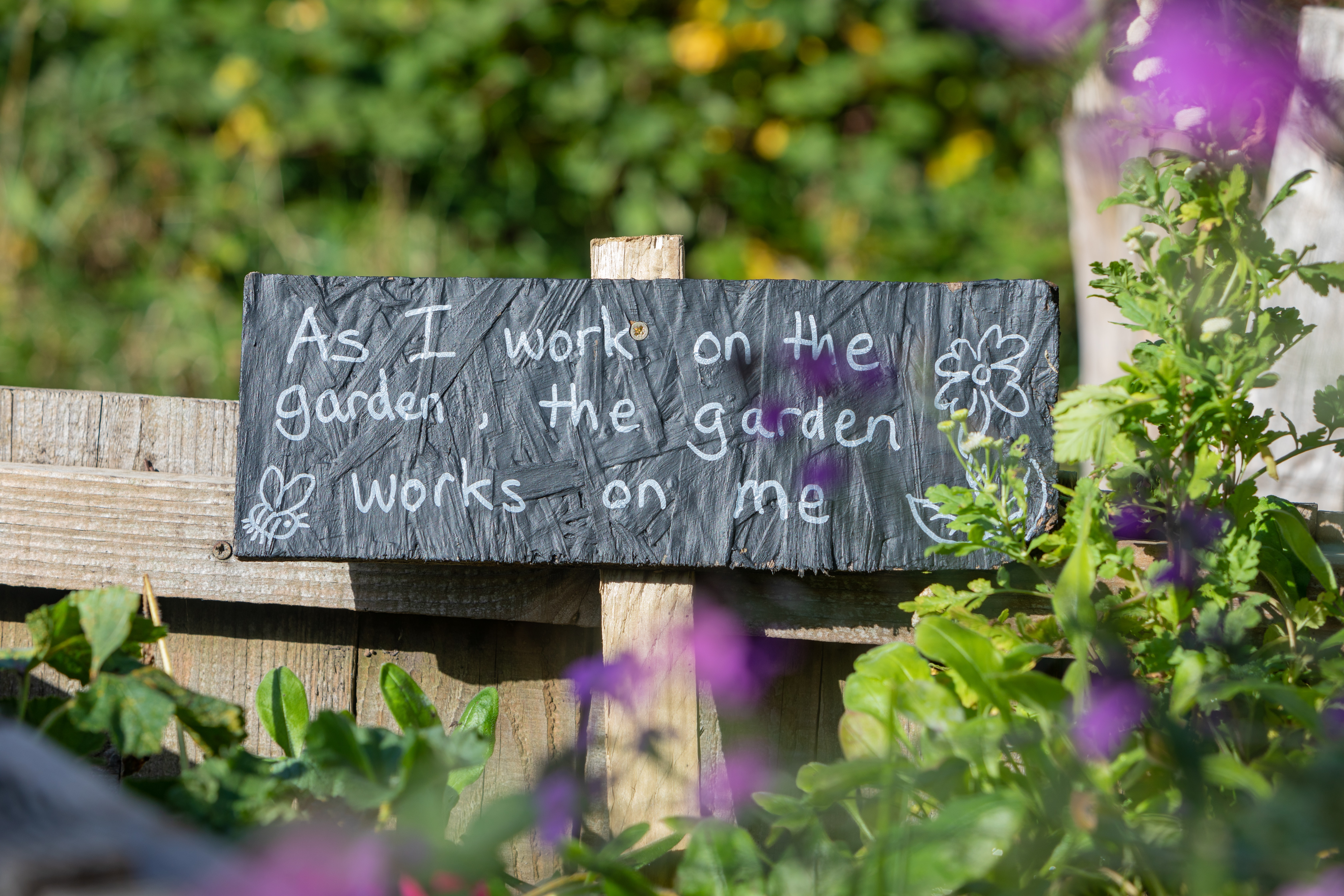 """A sign reads """"As I work on the garden, the garden works on me"""". Mental health benefits of gardening."""