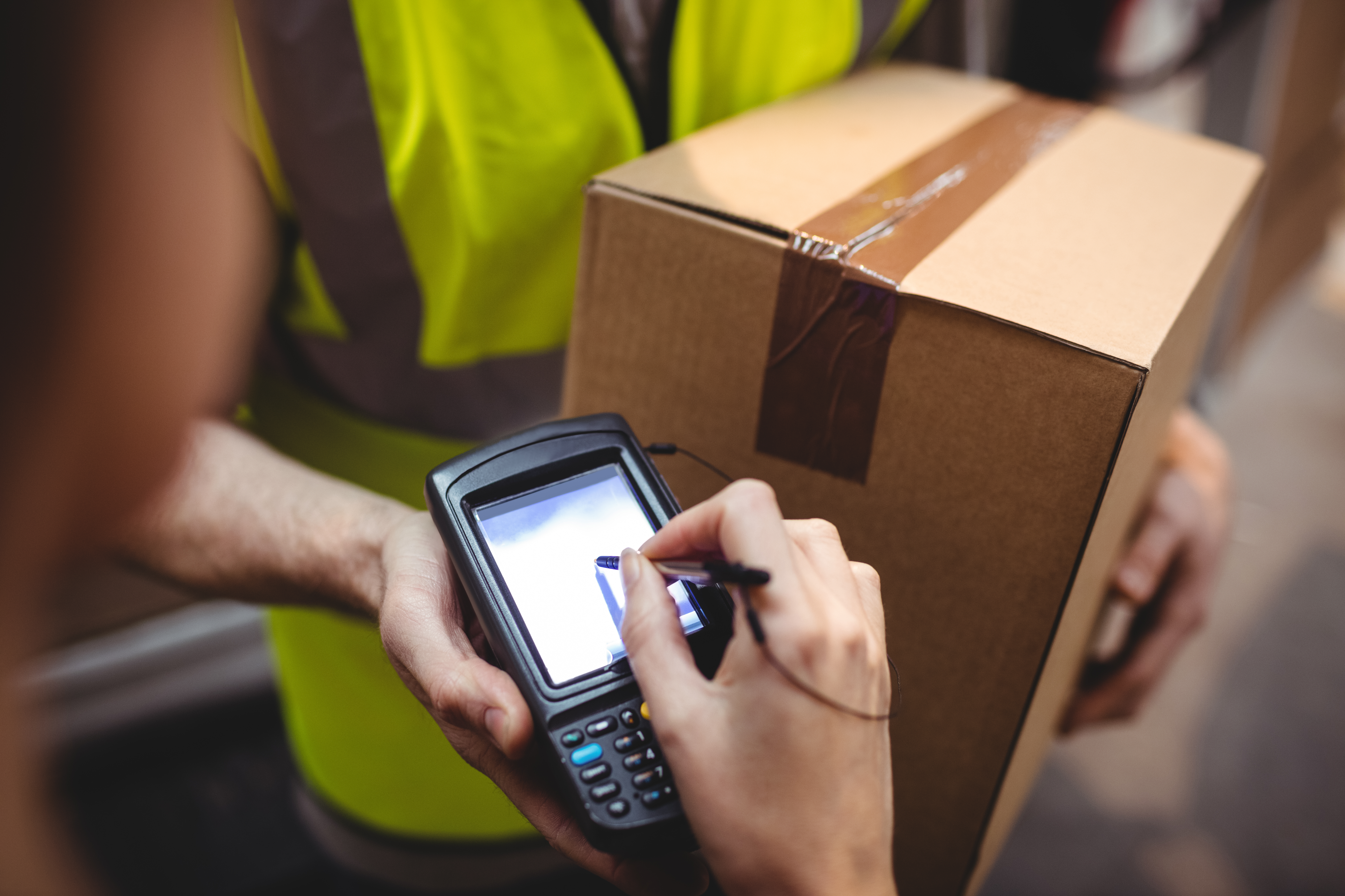 Someone signing on device for delivery