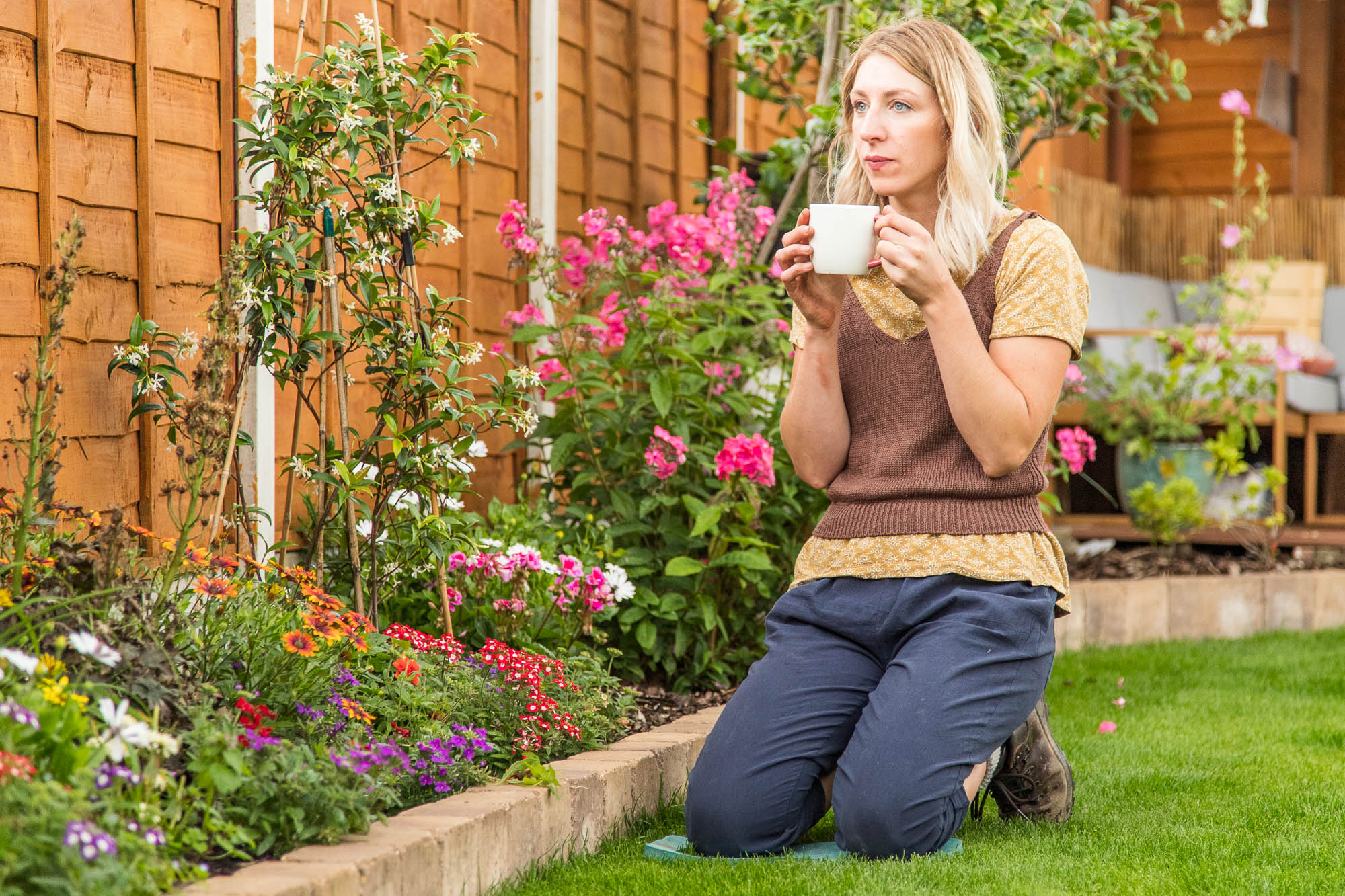 sarah kneeling in her garden with a cup of tea, contemplating the benefits of gardening for mental health