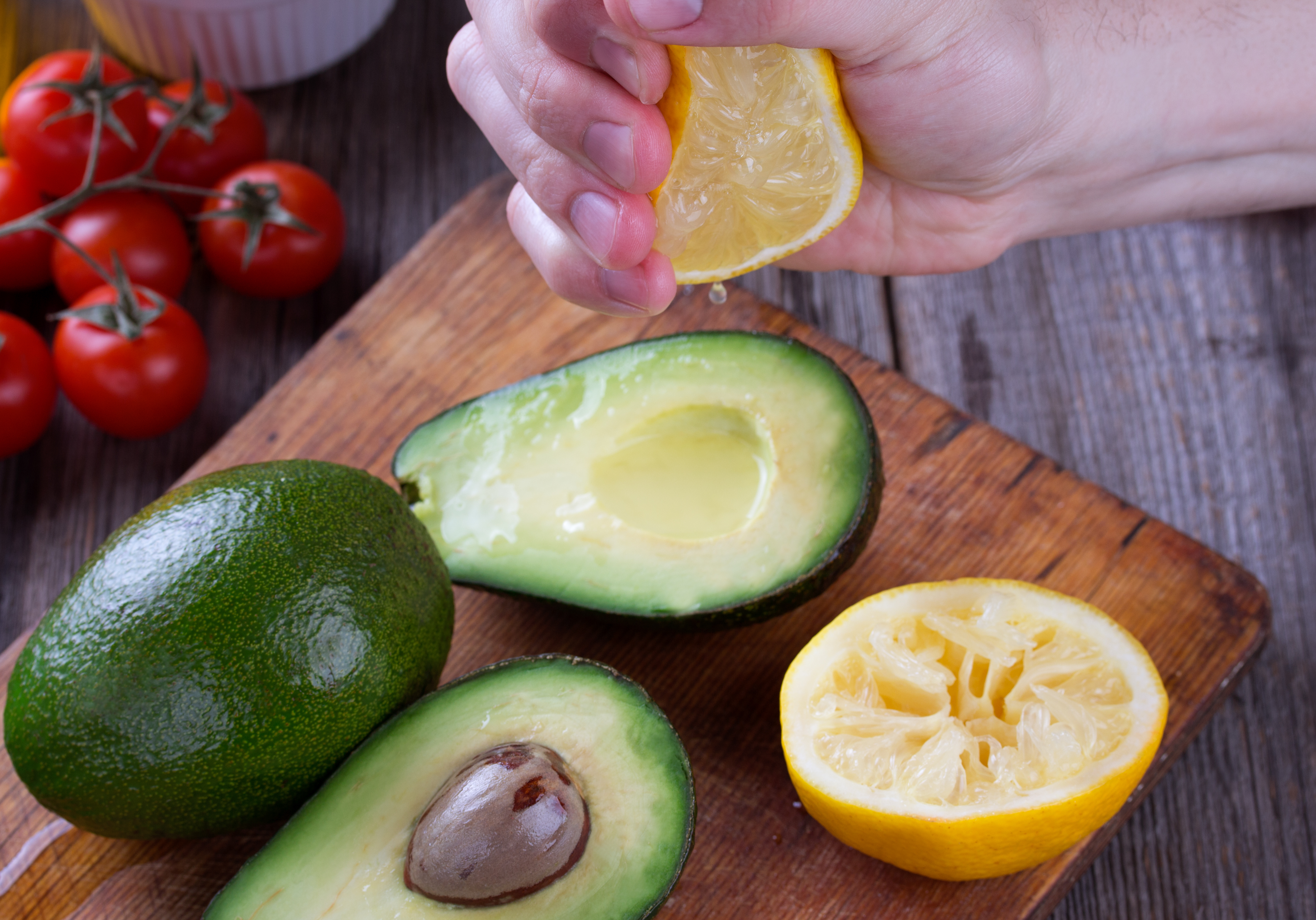 Someone using a lemon to stop avocados from browning by squeezing on the juice