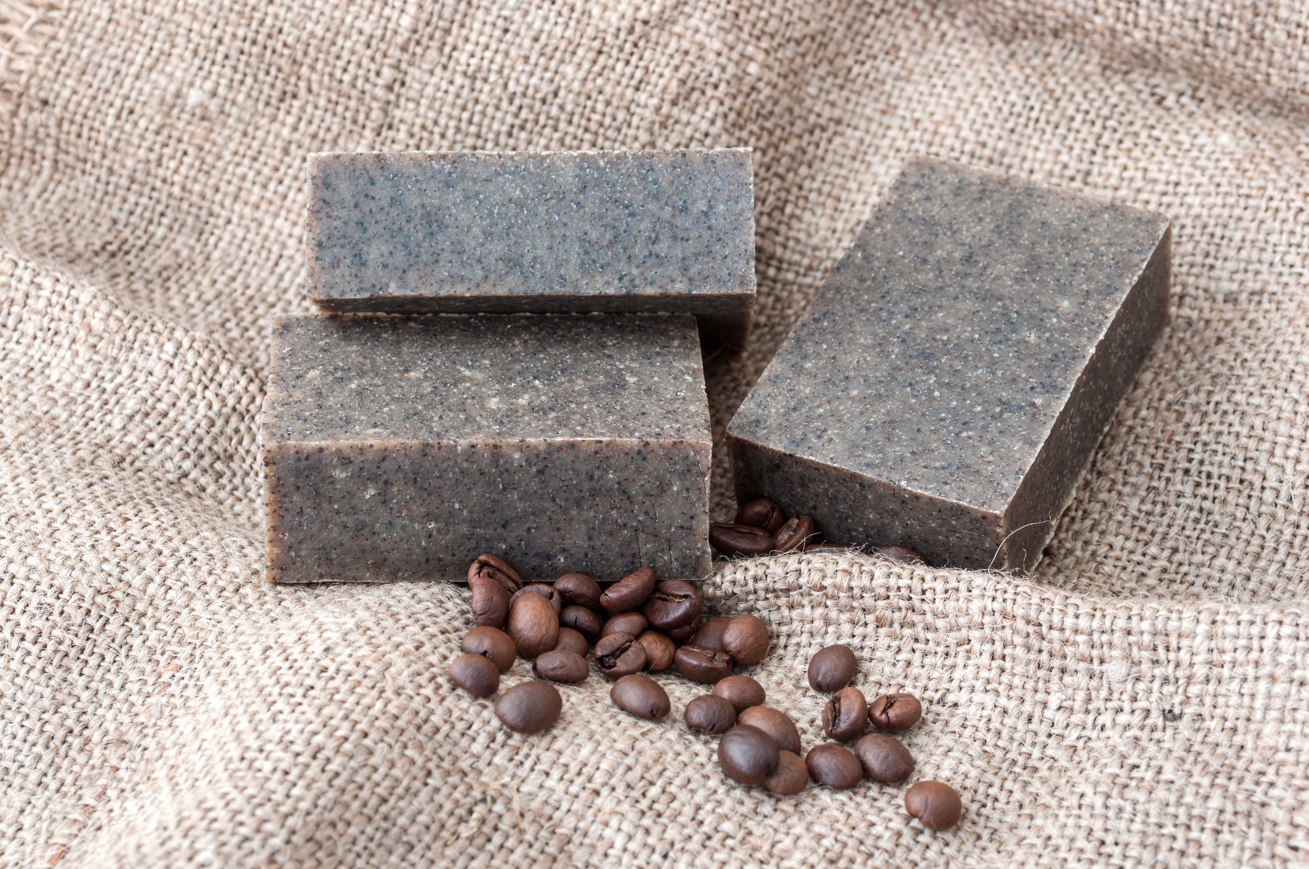 Coffee grounds soap bars laying on some hessian material with whole coffee beans in front of them