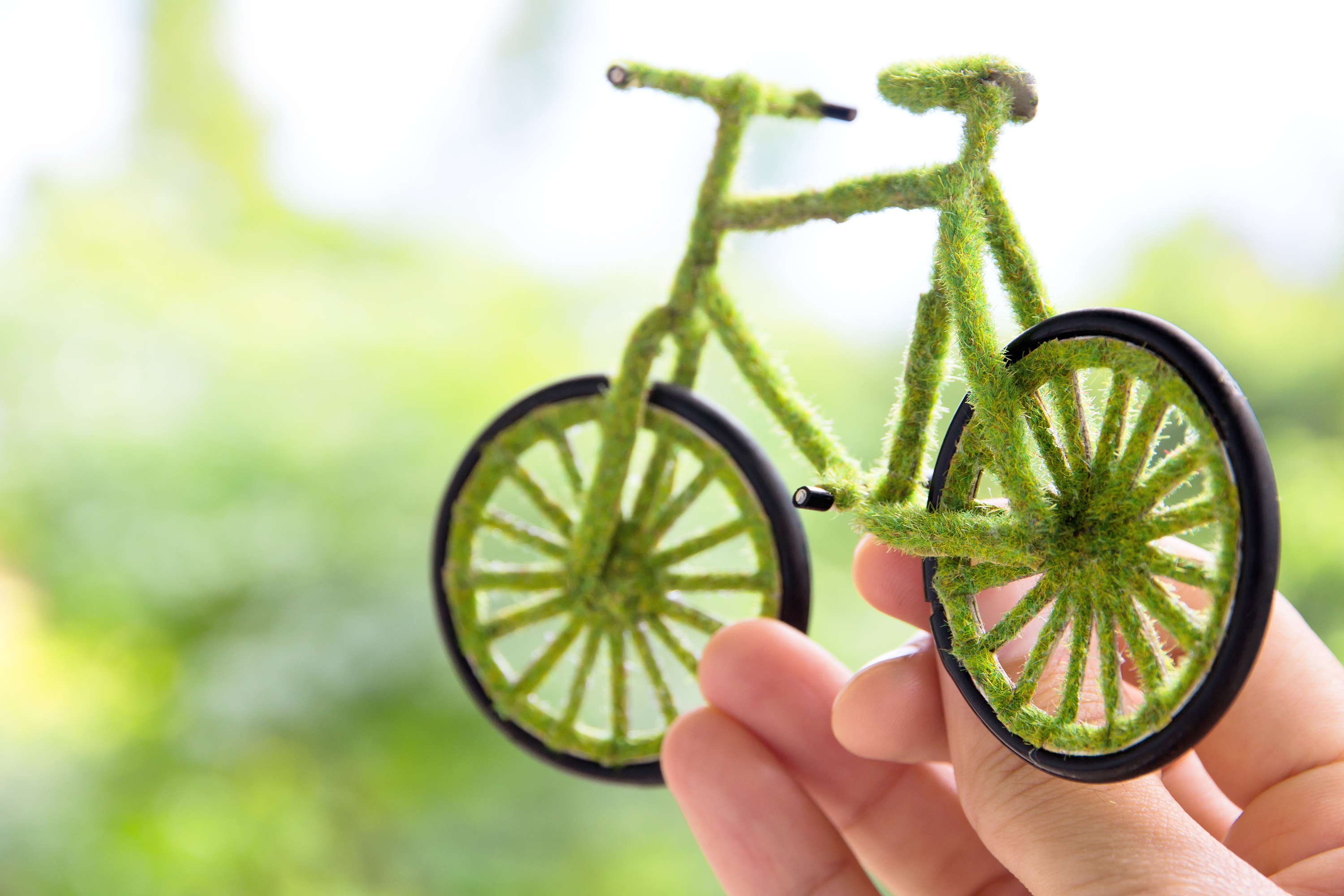 """an """"eco bike"""" covered in moss and greenery, being held up by someone's hand"""